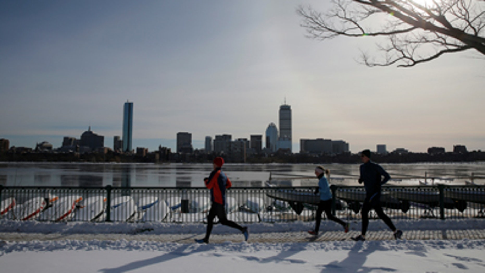 Joggers run along the Charles River past the Boston skyline on a sunny winter's day in Cambridge, Massachusetts, U.S. January 9, 2017. REUTERS/Brian Snyder - RTX2Y72G