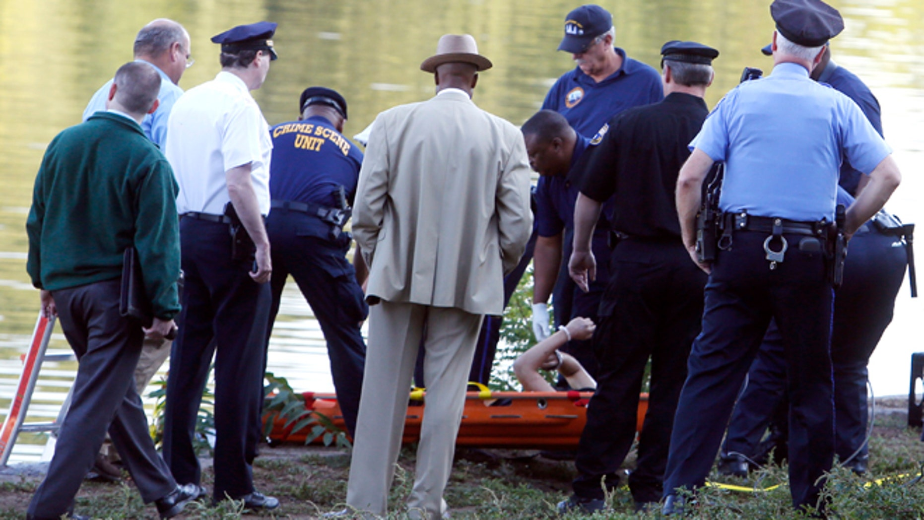 Aug. 27: Philadelphia police and other law enforcement officials view a body pulled from the Schuylkill River in Fairmount Park in Philadelphia. The bound bodies of two people were found in the river Wednesday, and a third man who said he managed to free himself is being treated at a hospital for stab wounds, police said.