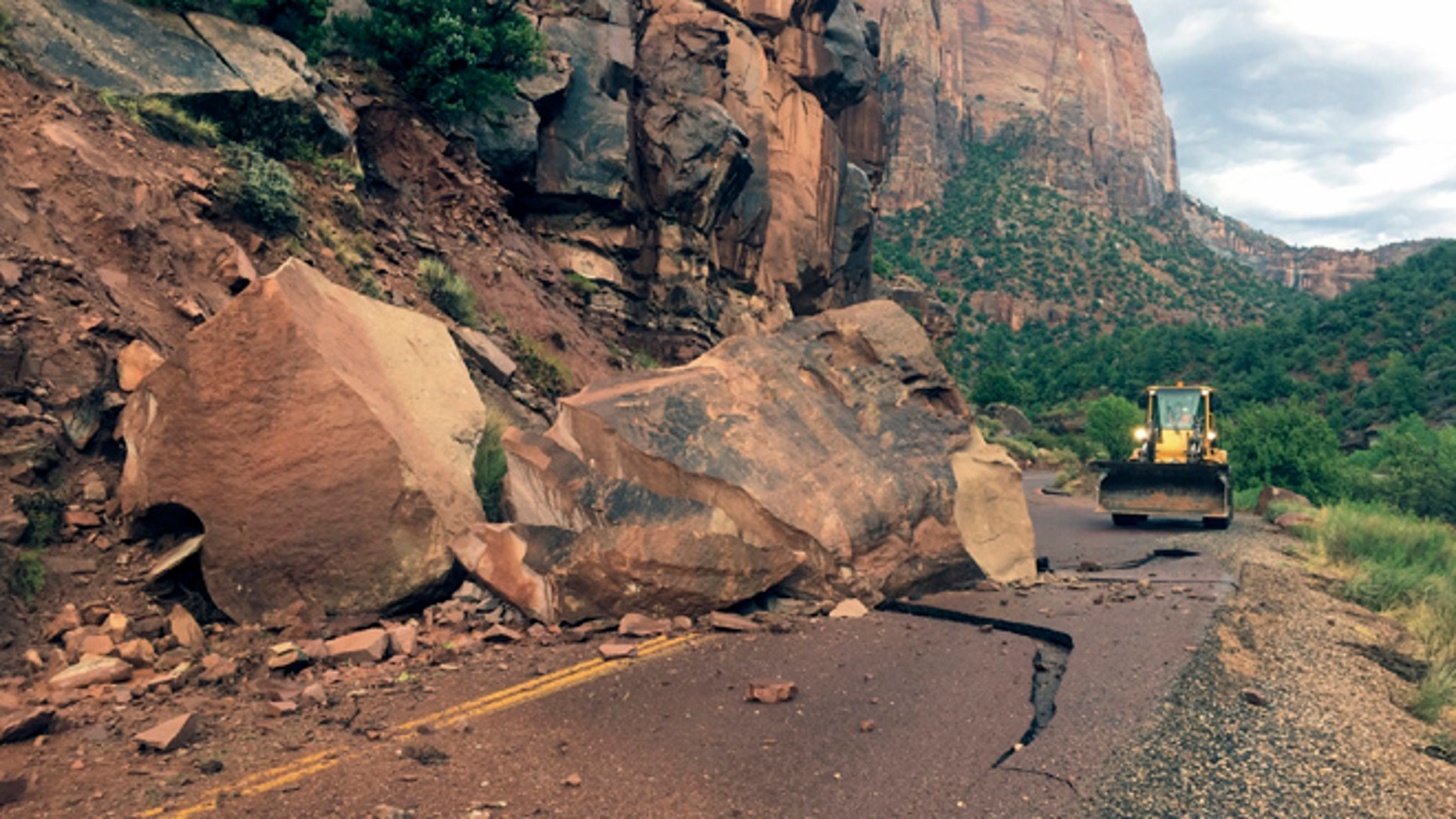 This Wednesday, Aug. 10, 2016 photo provided by the National Park Service shows the Zion- Mount Carmel Highway, State Route 9 closed, in Zion National Park after a boulder tumbled onto the roadway.