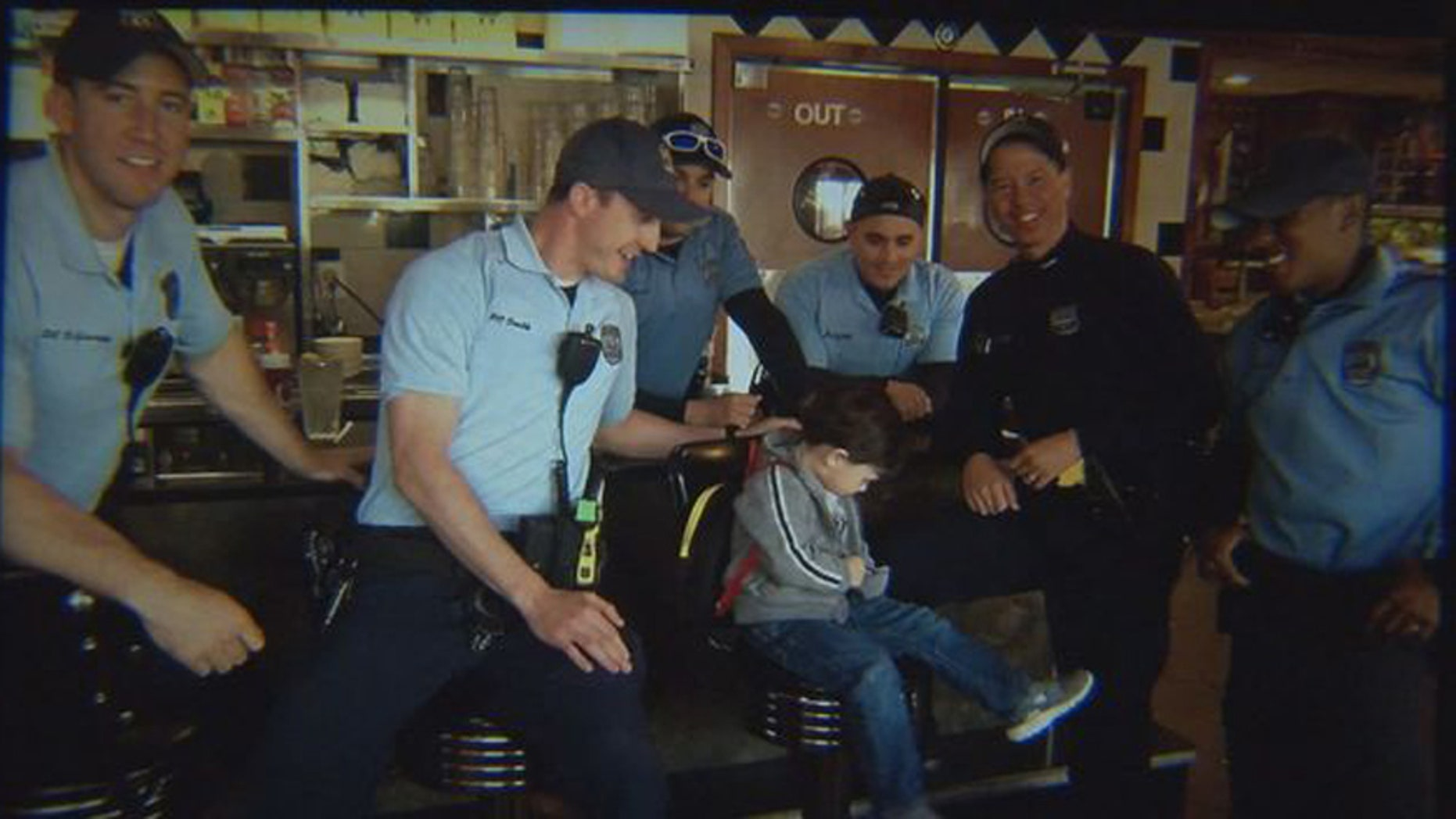 Logan, 3, and a group of police officers for whom he bought coffee.