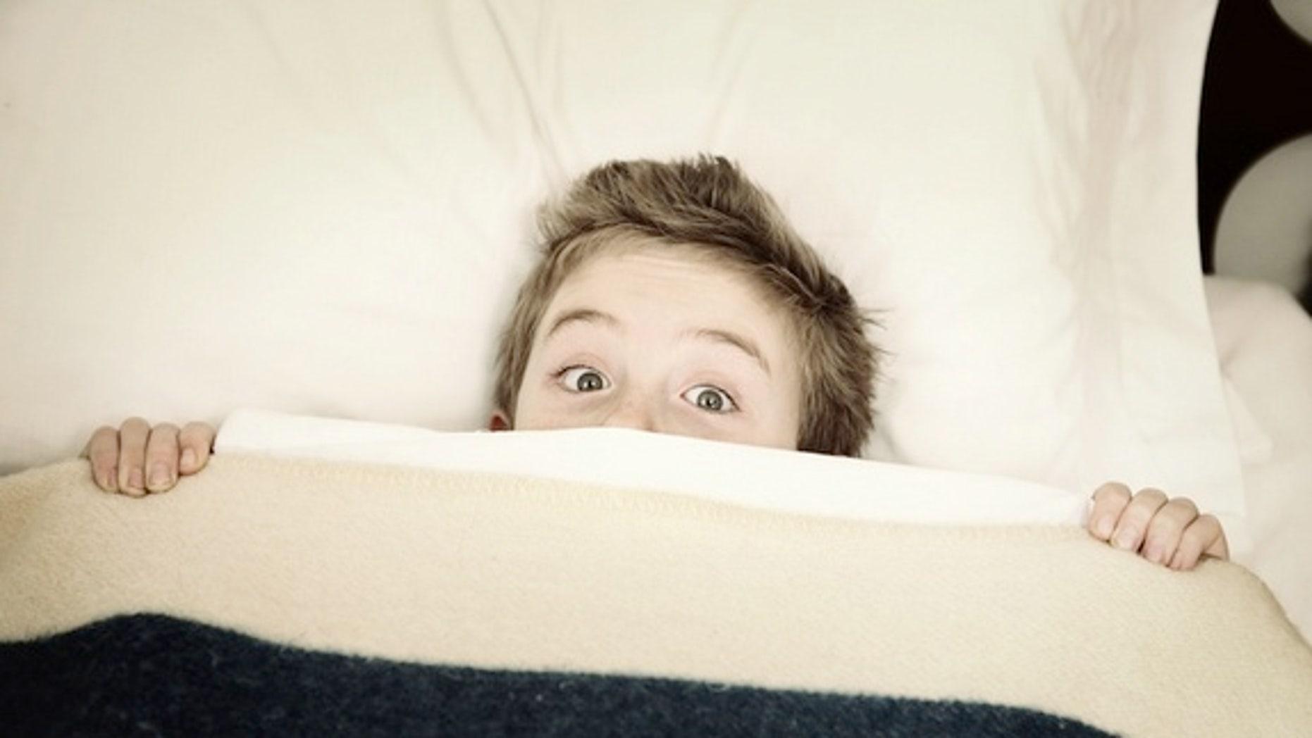 Boy hiding in bed.
