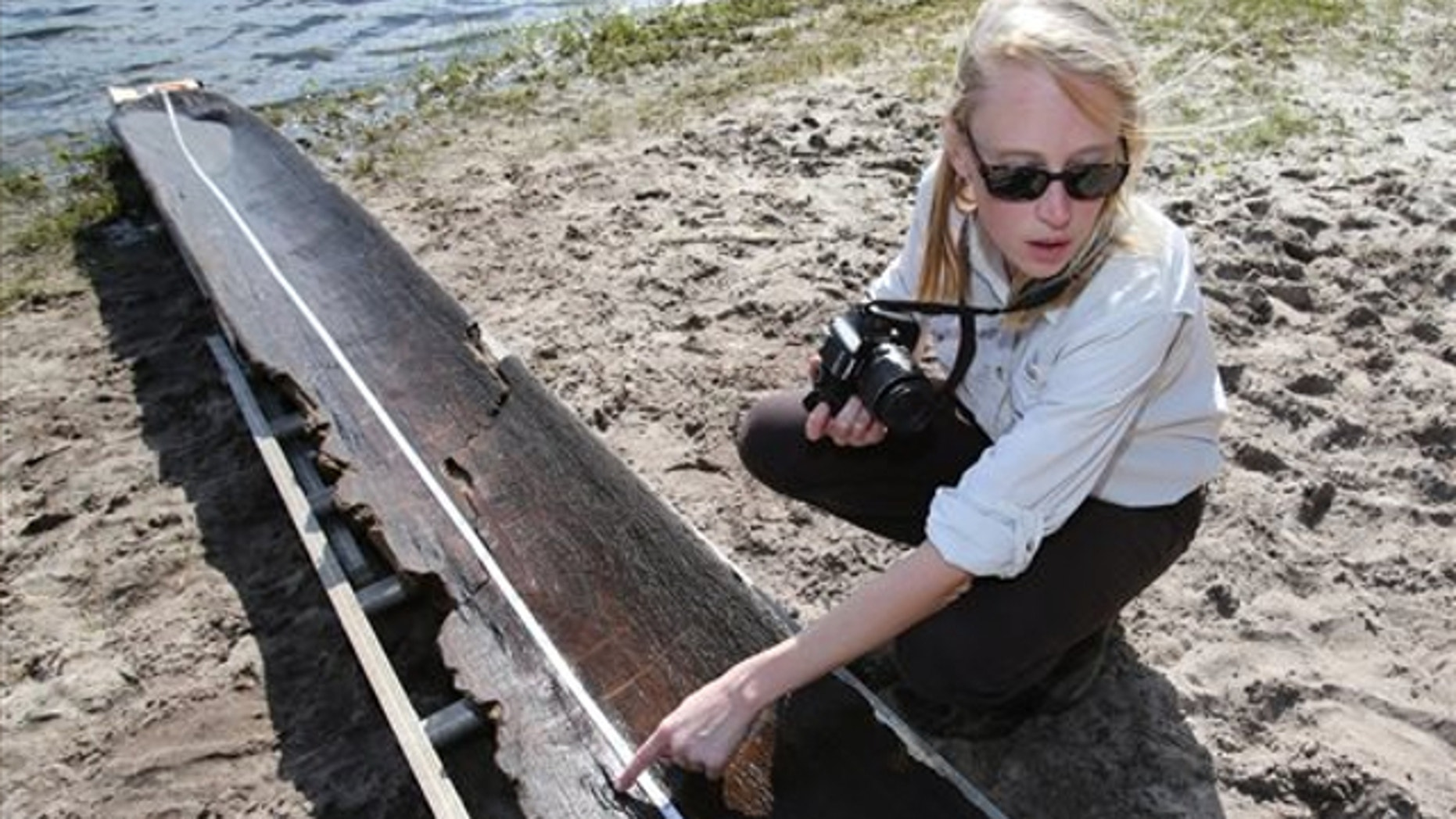 Sept. 19, 2013: Julia Byrd, a senior archaeologist with the Florida Bureau of Archaeological Research points out a burn mark on a dugout canoe found in Owen Lake in the Ocala National Forest east of Ocala, Fla.