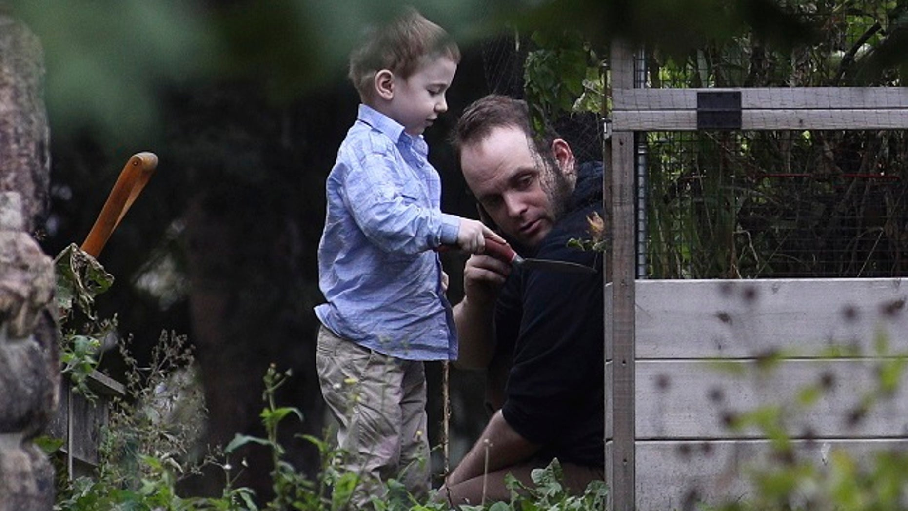 Joshua Boyle and his son Jonah play in the garden at his parent's house in Smiths Falls, Ontario, on Saturday, Oct. 14, 2017.