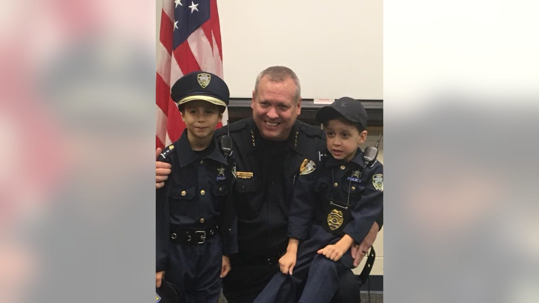 """Kissimmee Police Sgt. Sam Howard and Enzo Russell (left) pose for a picture after the 6-year-old was """"sworn in."""""""