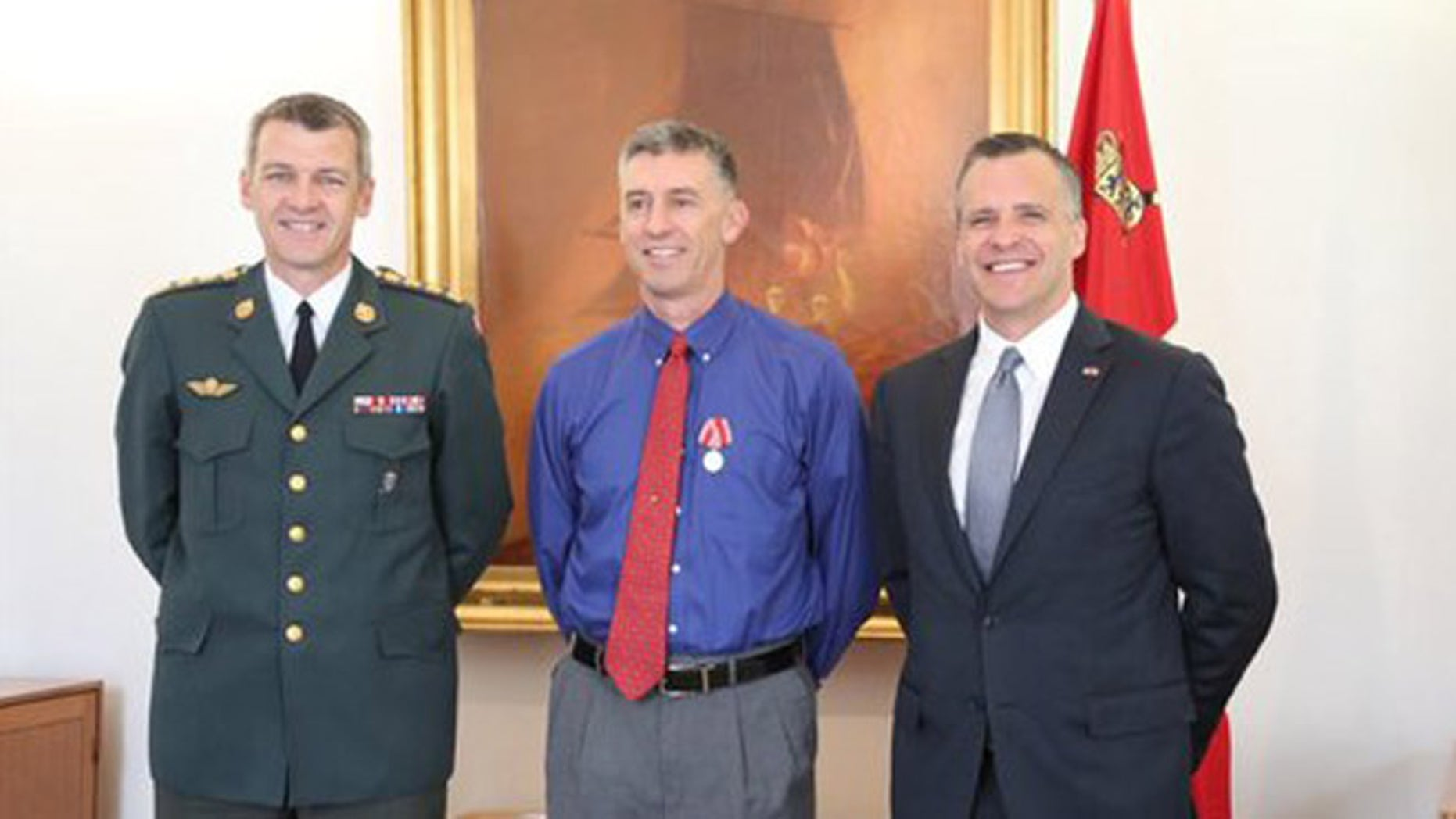 Danish Defense head Peter Bartram, U.S. Army Capt. Bradley Grimm and U.S. Ambassador to Denmark Rufus Gifford at Copenhagen medal ceremony. (Department of Defense)