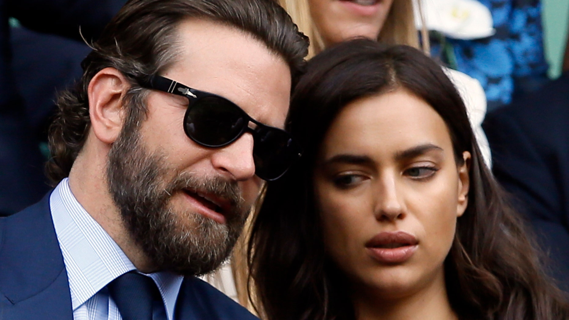 Actor Bradley Cooper, left, speaks with his girlfriend model Irina Shayk on the fourteenth day of the Wimbledon Tennis Championships in London, Sunday, July 10, 2016.