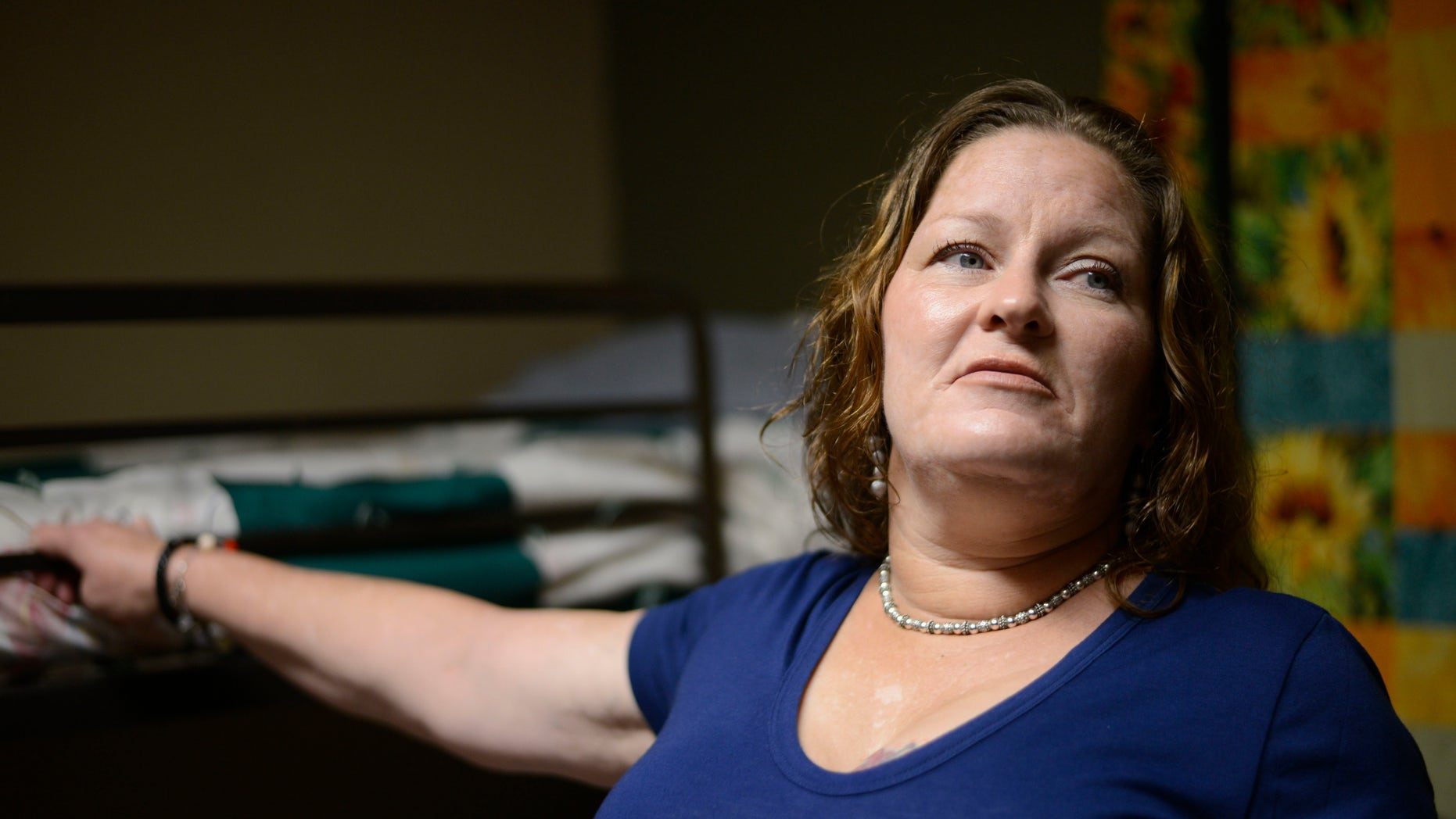 Susan Contreras stands next to her bed in a Phoenix-area shelter for victims of domestic violence on Wednesday, Aug. 3, 2016. Contreras is part of a unique program at the Barrow Neurological Institute in Phoenix that aims to assist abuse survivors who have suffered head trauma. (AP Photo/Beatriz Costa-Lima)