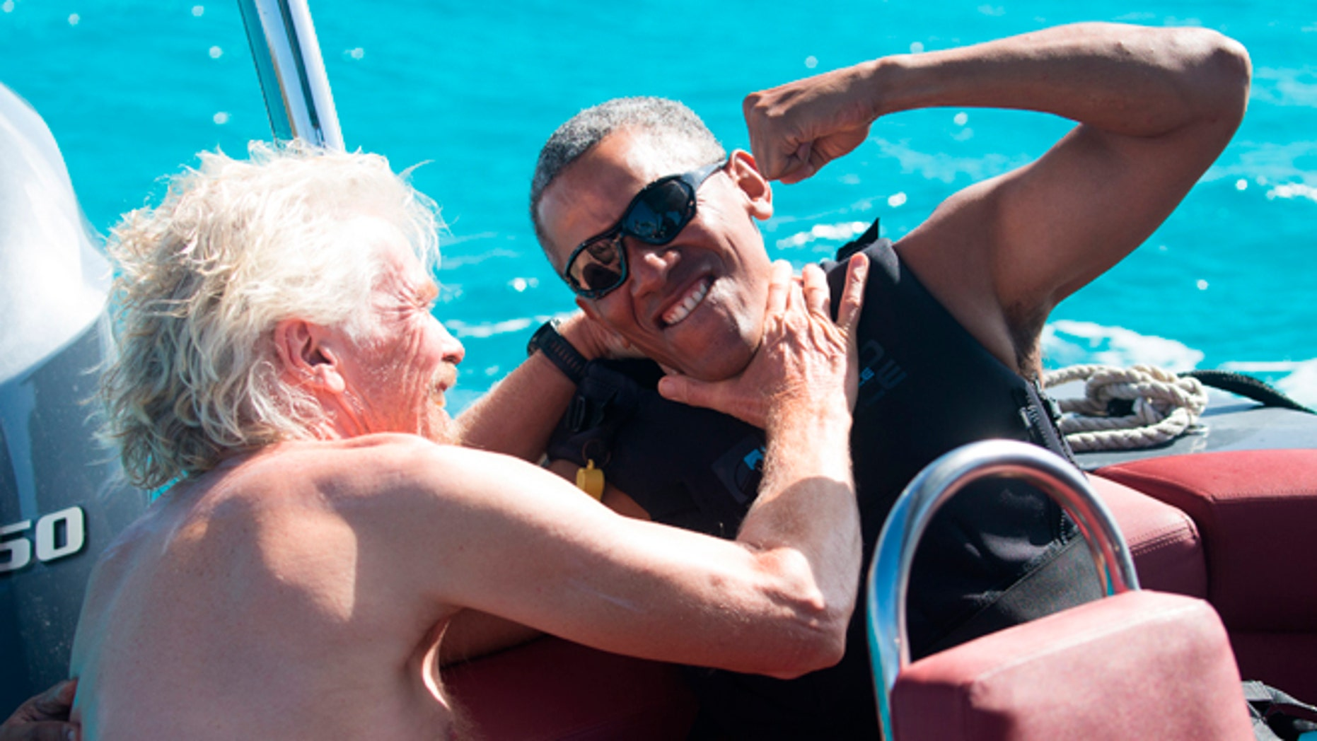 In this recent but undated photo made available by Virgin.com, former U.S President Barack Obama, jokes with Richard Branson, founder of the Virgin Group, during his stay on Moskito Island, British Virgin Islands.