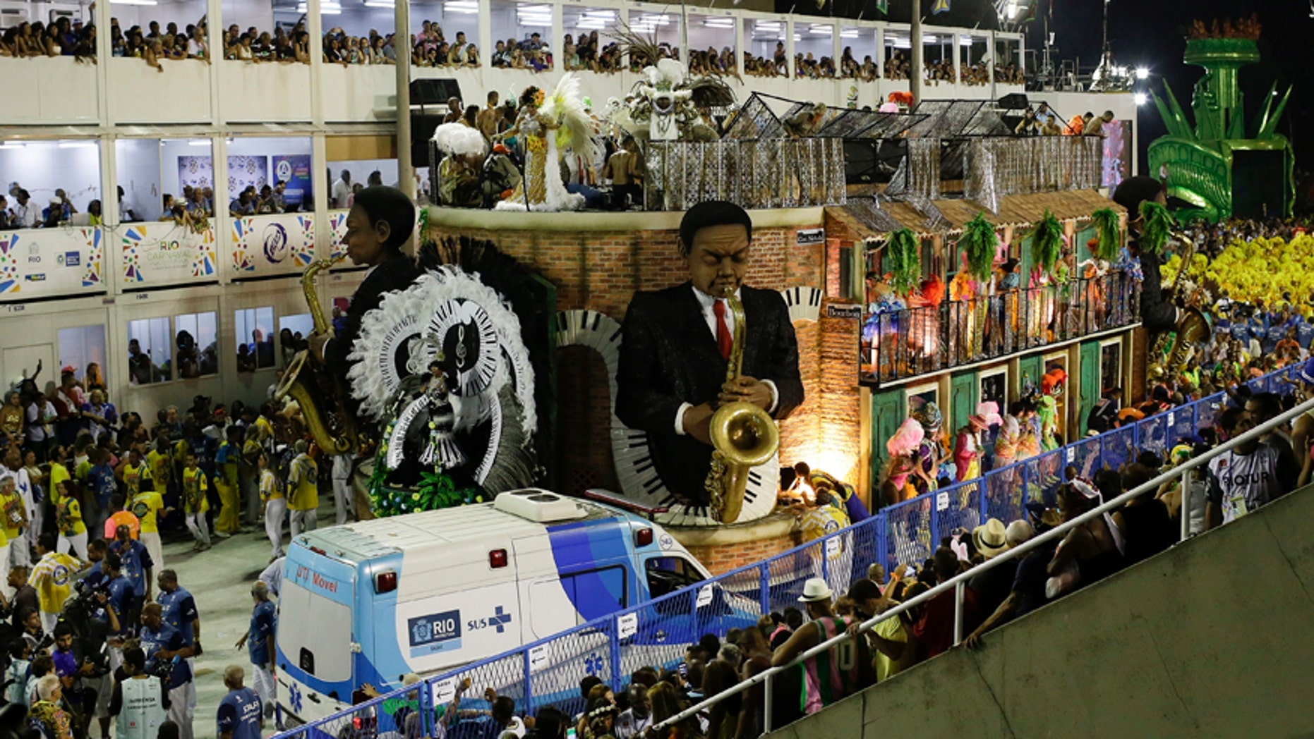 An ambulance parks in front the a float as people are rescued after an accident during the performing of the Unidos da Tijuca samba school for the Carnival celebrations at the Sambadrome in Rio de Janeiro, Brazil, Tuesday, Feb. 28, 2017. Part of the float has collapsed during Rio de Janeiro's world famous Carnival parade, injuring more than a dozen of people, according to doctors at the scene. (AP Photo/Leo Correa)