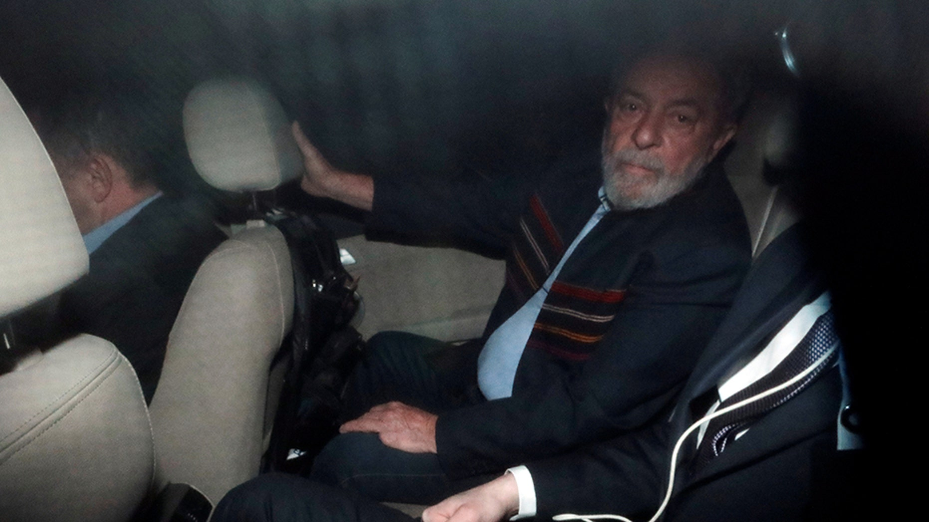 Former Brazilian President Luiz Inacio Lula da Silva, seen inside a car in Sao Paulo on Thursday, faced an arrest warrant.