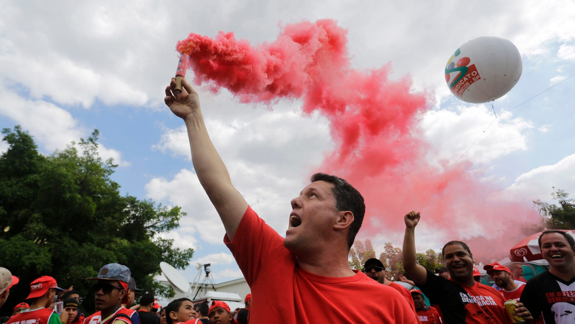 Demonstrators march in support of Brazilian President Dilma Rousseff and of the Worker's Party in front of Lula Institute, of former president Luiz Inacio Lula da Silva, in Sao Paulo, Brazil, Sunday, Aug. 16, 2015. The march in support of Rousseff came as other demonstrators are taking to the streets of cities and towns across Brazil for a day of nationwide anti-government protests. President Rousseff's second term in office has been shaken by a snowballing corruption scandal involving politicians from her Workersâ Party, as well as a spluttering economy, spiraling currency and rising inflation. (AP Photo/Nelson Antoine)