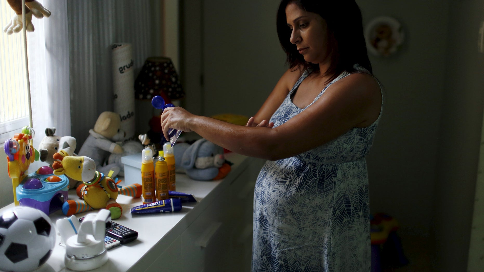 Gisele Felix, who is five months pregnant, applies repellent on her arm at her home in Rio de Janeiro, Brazil, January 28, 2016. Fear of the mosquito-borne Zika virus has Brazilians rushing to buy repellant, creating a shortage of some brands on pharmacy shelves and boosting sales for the industry - a trend some producers are preparing for elsewhere as the outbreak spreads. Picture taken January 28, 2016. REUTERS/Pilar Olivares - RTX25L1M