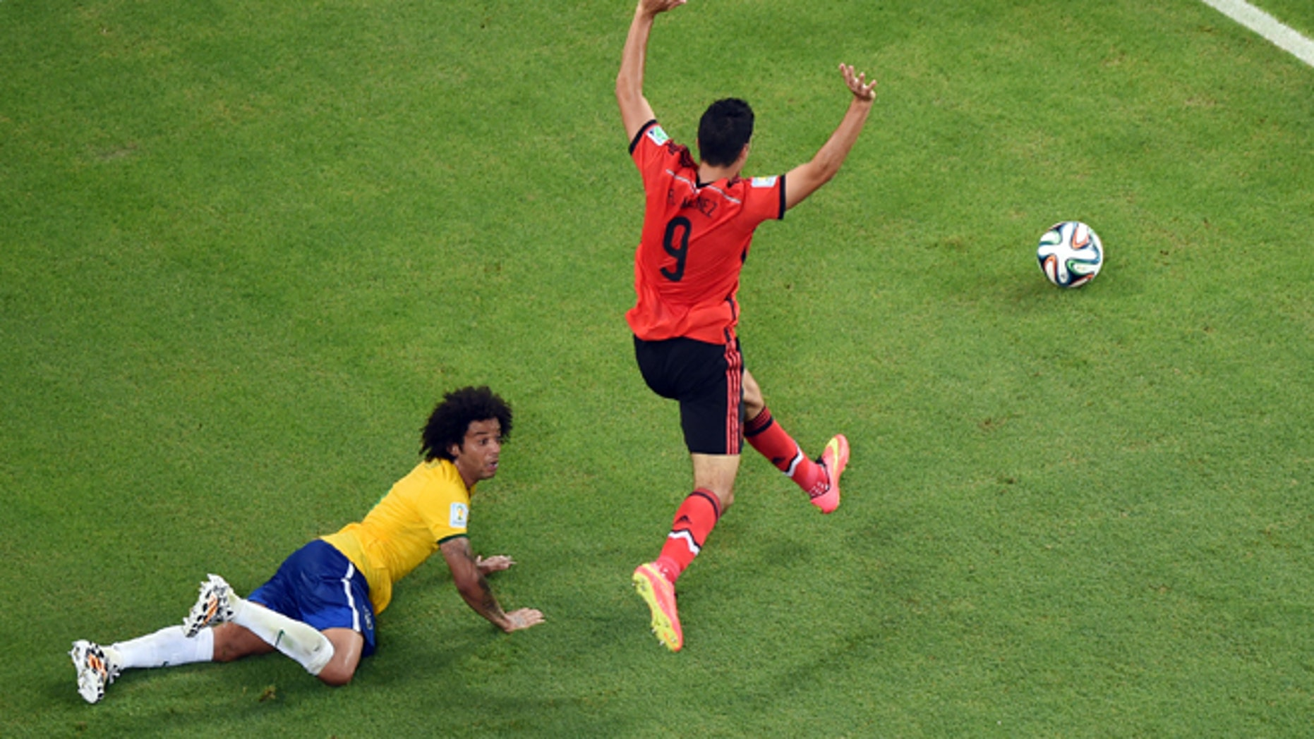 June 17, 2014: Brazil's Marcelo falls in the penalty box as Mexico's Raul Jimenez raises his arms during the group A World Cup soccer match between Brazil and Mexico at the Arena Castelao in Fortaleza, Brazil.