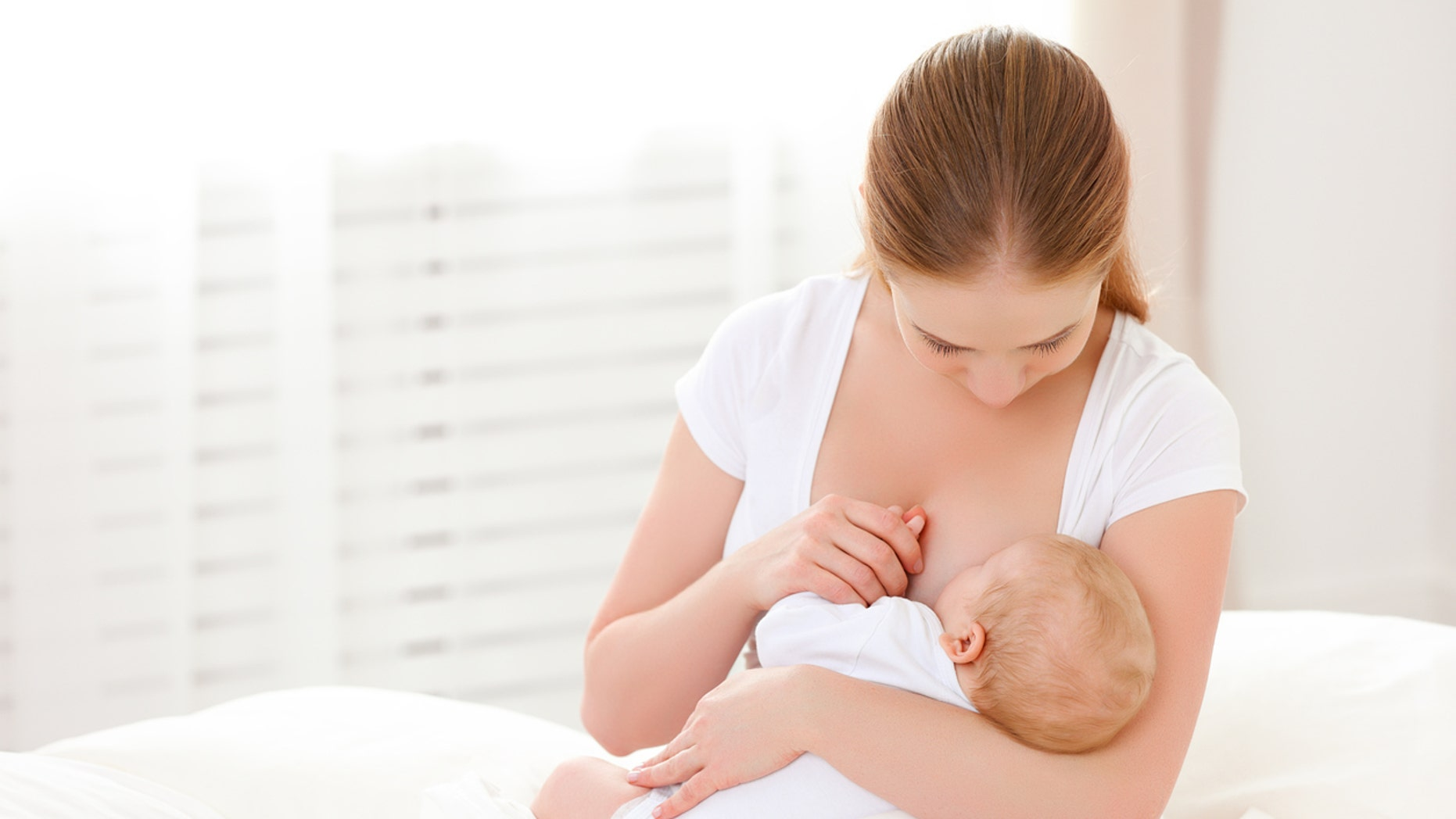 mother breastfeeding her newborn baby in a white bed