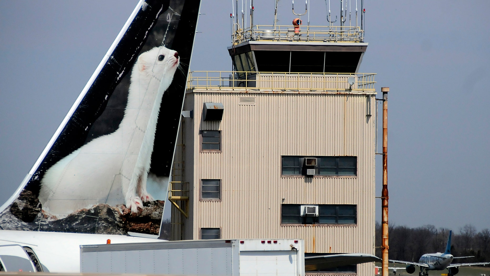 FILE - In this April 8, 2013, file photo, the painted tail appears on a Frontier Airlines aircraft parked at a gate at Trenton-Mercer Airport in Ewing, N.J. Four women pilots who fly for Frontier want the airline to change policies on maternity leave and make it easier for new mothers to pump breast milk once they have returned to work. The American Civil Liberties Union has filed discrimination charges with the Equal Employment Opportunity Commission on behalf of the four. (Jackie Schear/The Trentonian via AP)  TRENTON TIMES OUT; PHILLY METRO OUT; MANDATORY CREDIT