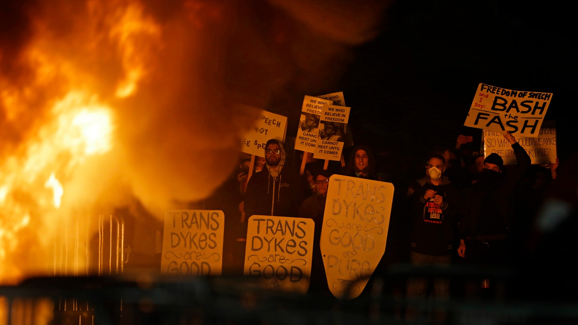 Protestors watch a bonefire on Sproul Plaza during a rally against the scheduled speaking appearance by Breitbart News editor Milo Yiannopoulos on the University of California at Berkeley campus on Wednesday, Feb. 1, 2017, in Berkeley, Calif. The event was canceled out of safety concerns after protesters hurled smoke bombs, broke windows and started a bonfire. (AP Photo/Ben Margot)