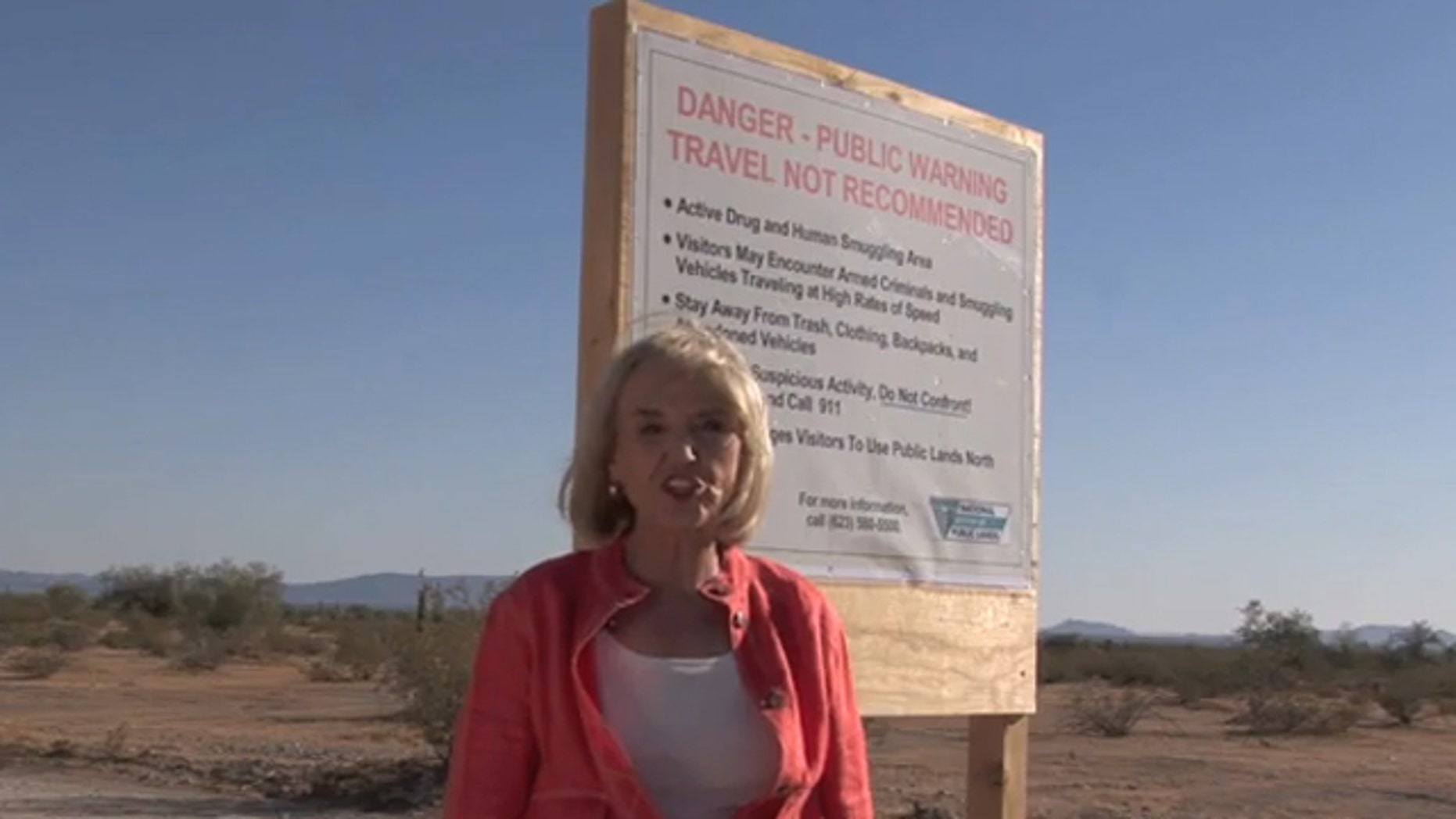 Arizona Gov. Jan Brewer is shown next to a warning sign in the desert in a campaign ad. (Governor Jan Brewer 2010)