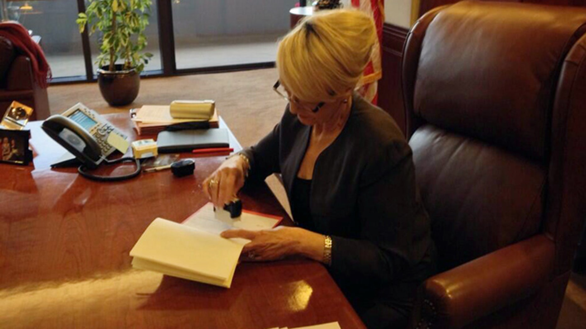 Feb. 26, 2014: In this photo tweeted by the office of Arizona Gov. Jan Brewer, Brewer vetoes Senate Bill 1062.