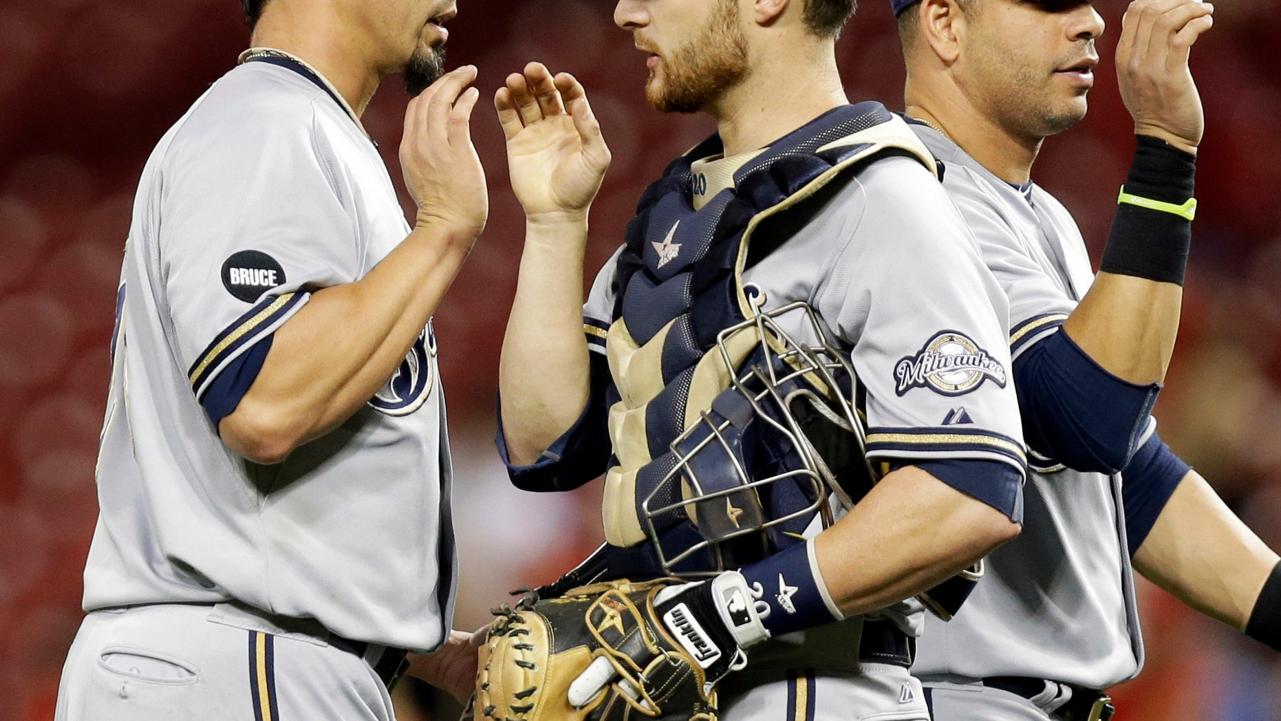 Sept. 24, 2014: In this file photo, Milwaukee Brewers starting pitcher Kyle Lohse, left, is congratulated by catcher Jonathan Lucroy, center, after the Brewers defeated the Cincinnati Reds 5-0 in a baseball game in Cincinnati.