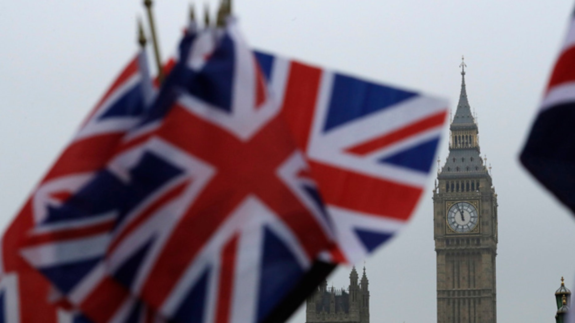 Union flags displayed on a tourist stall, backdropped by the Houses of Parliament and Elizabeth Tower containing the bell know as Big Ben, in London, Wednesday, Feb. 8, 2017.