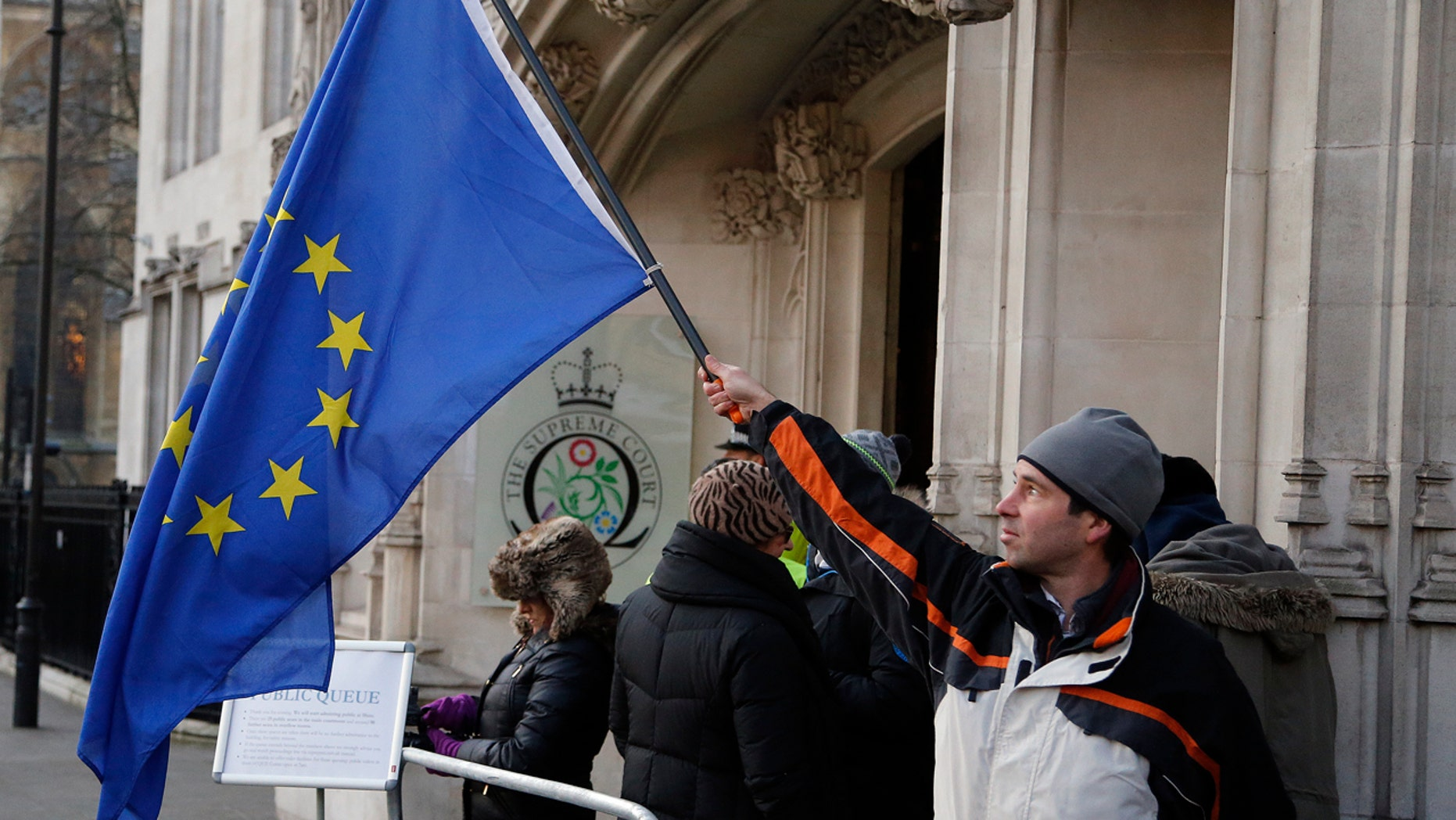 A man waves a European flag in front of the Supreme Court in London, Monday, Dec. 5, 2016.