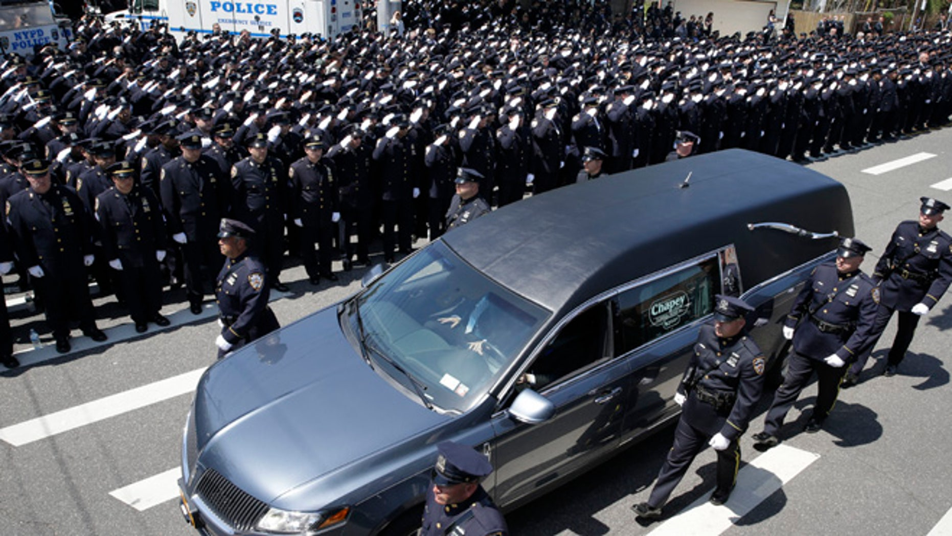 May 8, 2015: Police officers salute as the procession for New York City Police officer Brian Moore passes after his funeral mass at the St. James Roman Catholic church in Seaford, N.Y.