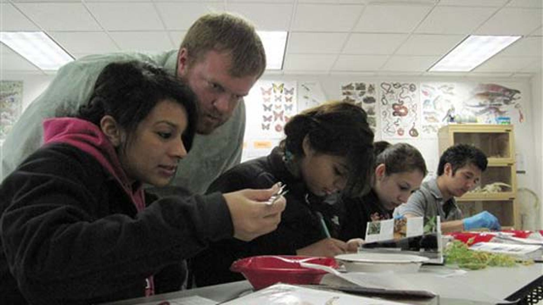 Xenia Valdovinos, left, and her teacher, Eric Schmidt, examine insects found outside Bridgeport High School in Bridgeport, Wash. on Thursday, May 5, 2011. Schmidt teaches a college biology course at the high school, which is in the running to have President Barack Obama deliver the commencement address. (AP Photo/Shannon Dininny)