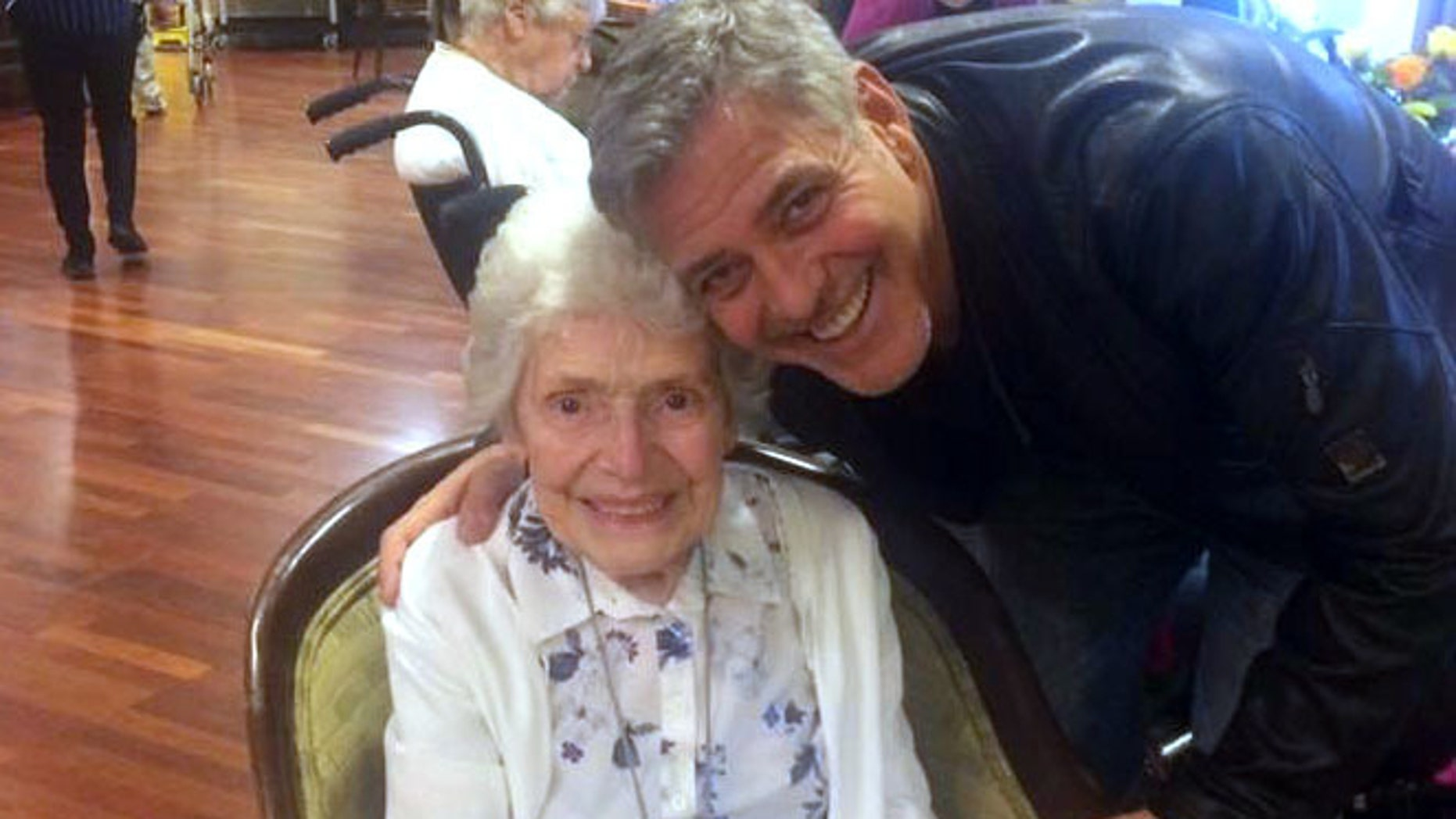 In this photo taken on Sunday, March 19, 2017, US actor George Clooney visits 87-year-old Pat Adams at Sunrise of Sonning Retirement and Assisted Living Facility in Reading, England. Actor George Clooney startled an 87-year-old fan in Britain by showing up at her assisted living facility with flowers and a card to wish her a happy birthday. (Linda Jones/Sunrise of Sonning Retirement and Assisted Living Facility via AP)