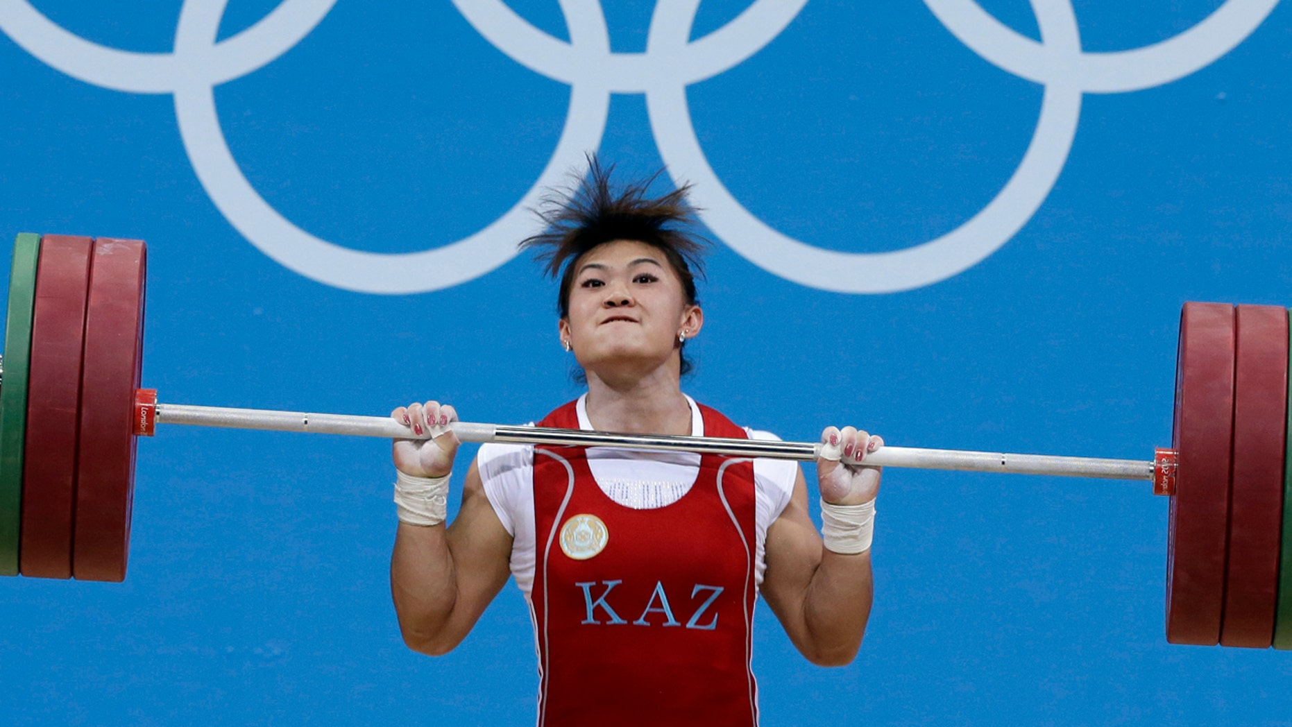 FILE - A Tuesday, July 31, 2012, photo from files of Maiya Maneza of Kazakhstan competing during the women's 63-kg, group A, weightlifting competition at the 2012 Summer Olympics, in London.