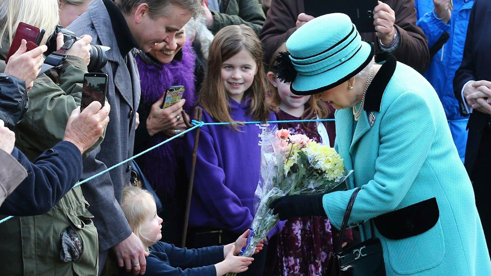Britain's Queen Elizabeth II stops to receive flowers from 3-year old Jessica Atfield, after the queen and her husband Duke of Edinburgh, attended a church service at St Peter and St Paul church in West Newton, England, Sunday Feb. 5, 2017.