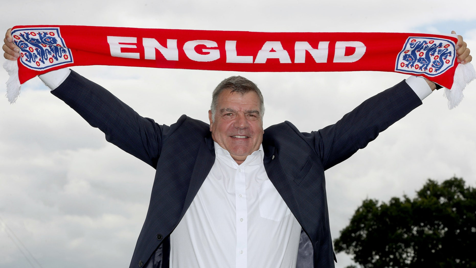 July 25, 2016: Newly appointed England manager Sam Allardyce displays an England scarf, in Burton-on-Trent, England.