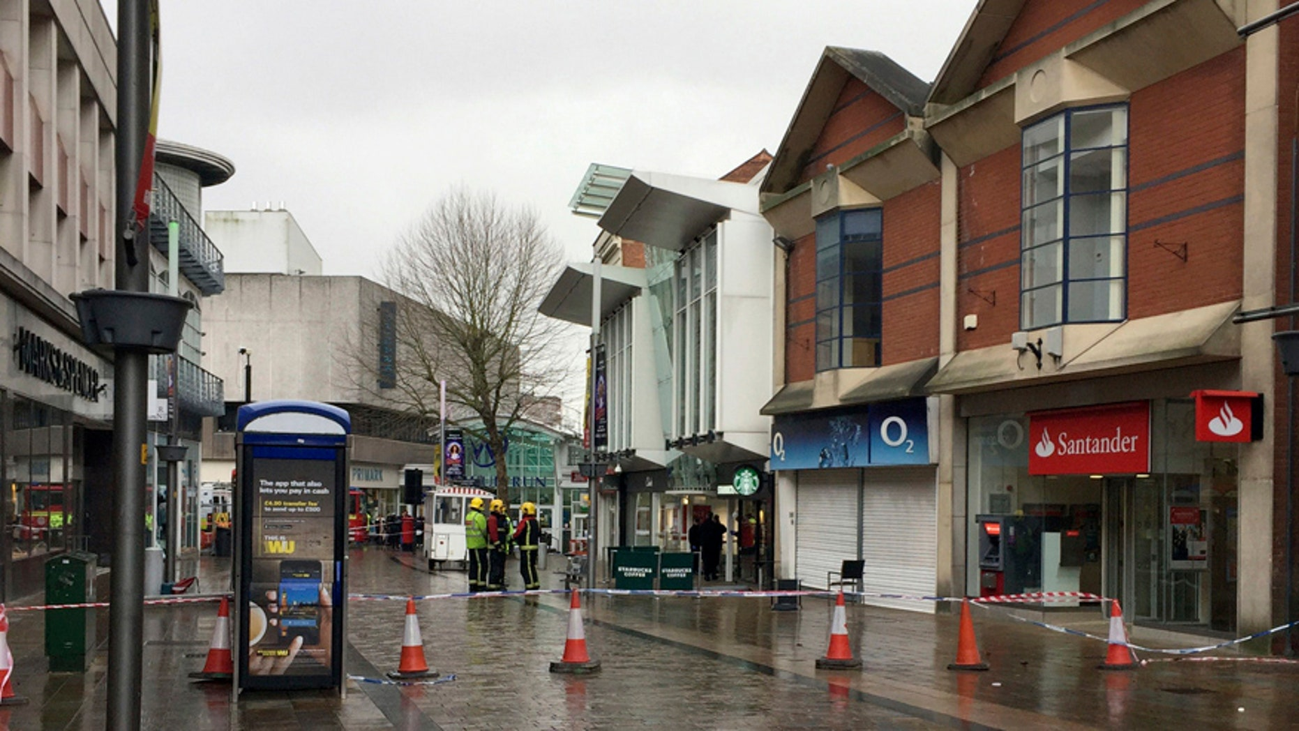 """The scene in Wolverhampton city center after a woman died when she was hit by a piece of roof the """"size of a coffee table"""" during strong winds, Wolverhampton, England, Thursday, Feb. 23, 2017. Flights have been cancelled and commuters were warned they faced delays after Storm Doris reached nearly 90mph. (Matthew Cooper/PA via AP)"""