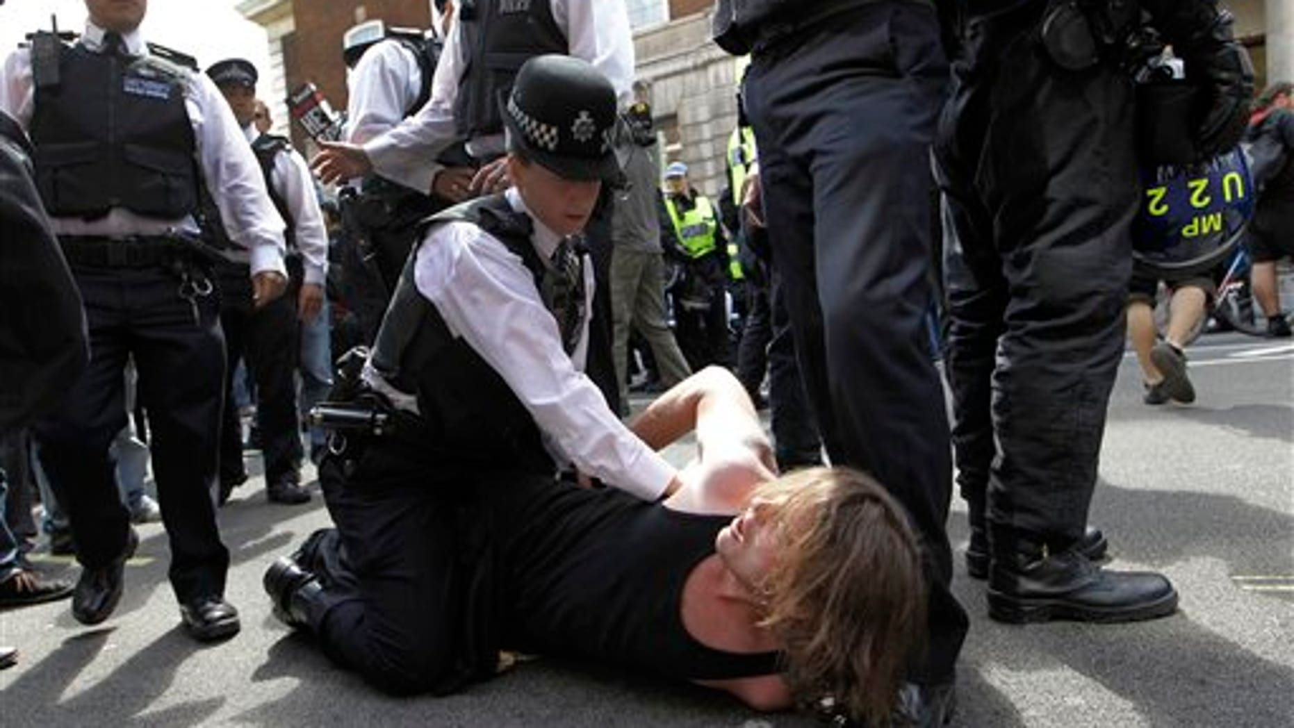June 30: A British police officer holds down a protester in Whitehall, London as thousands of public sector workers and teachers protest in central London in a one day strike over pension and government cuts. British teachers and public service workers swapped classrooms and offices for picket lines as hundreds of thousands walked off the job to protest pension cuts.
