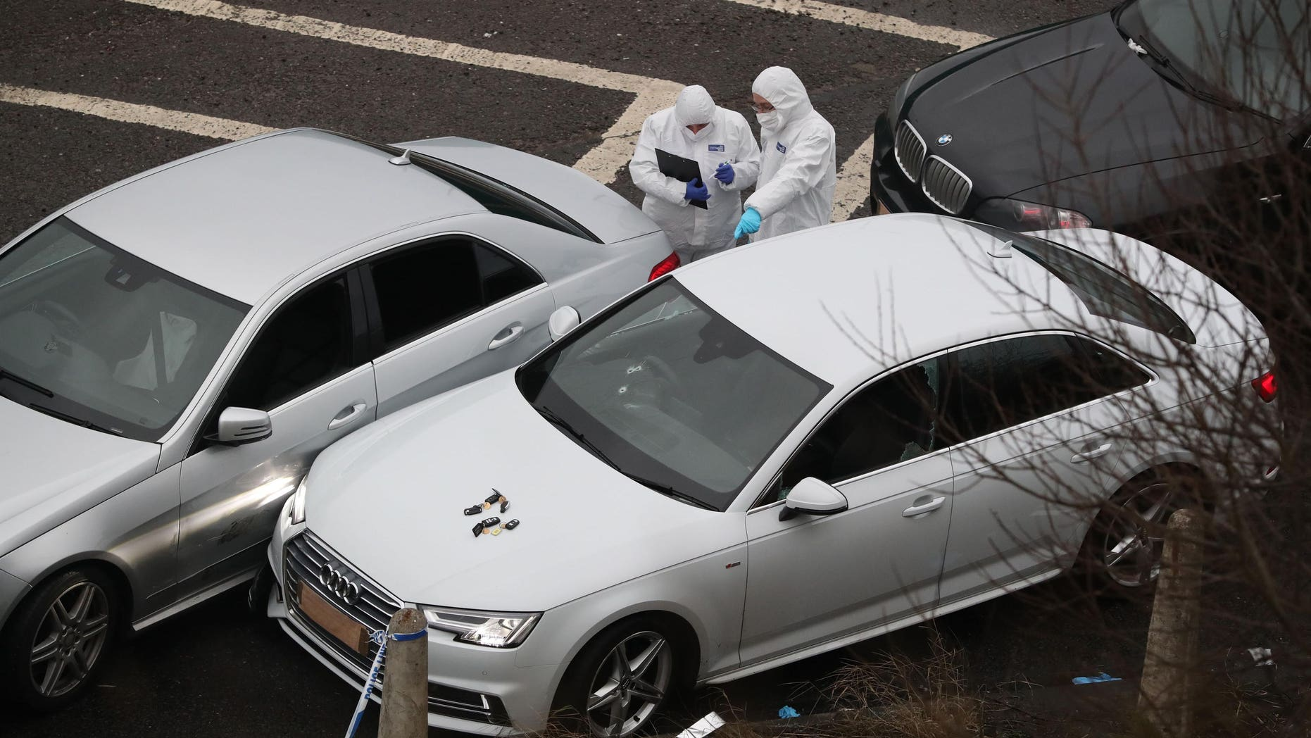Police forensic officers examine a silver Audi with bullet holes in the windscreen at the scene near the M62 motorway in Huddersfield, England, early Tuesday Jan. 3, 2017.  An unidentified man died in a police shooting Monday evening during a police operation, with no other details released by the authorities. (Peter Byrne / PA via AP)