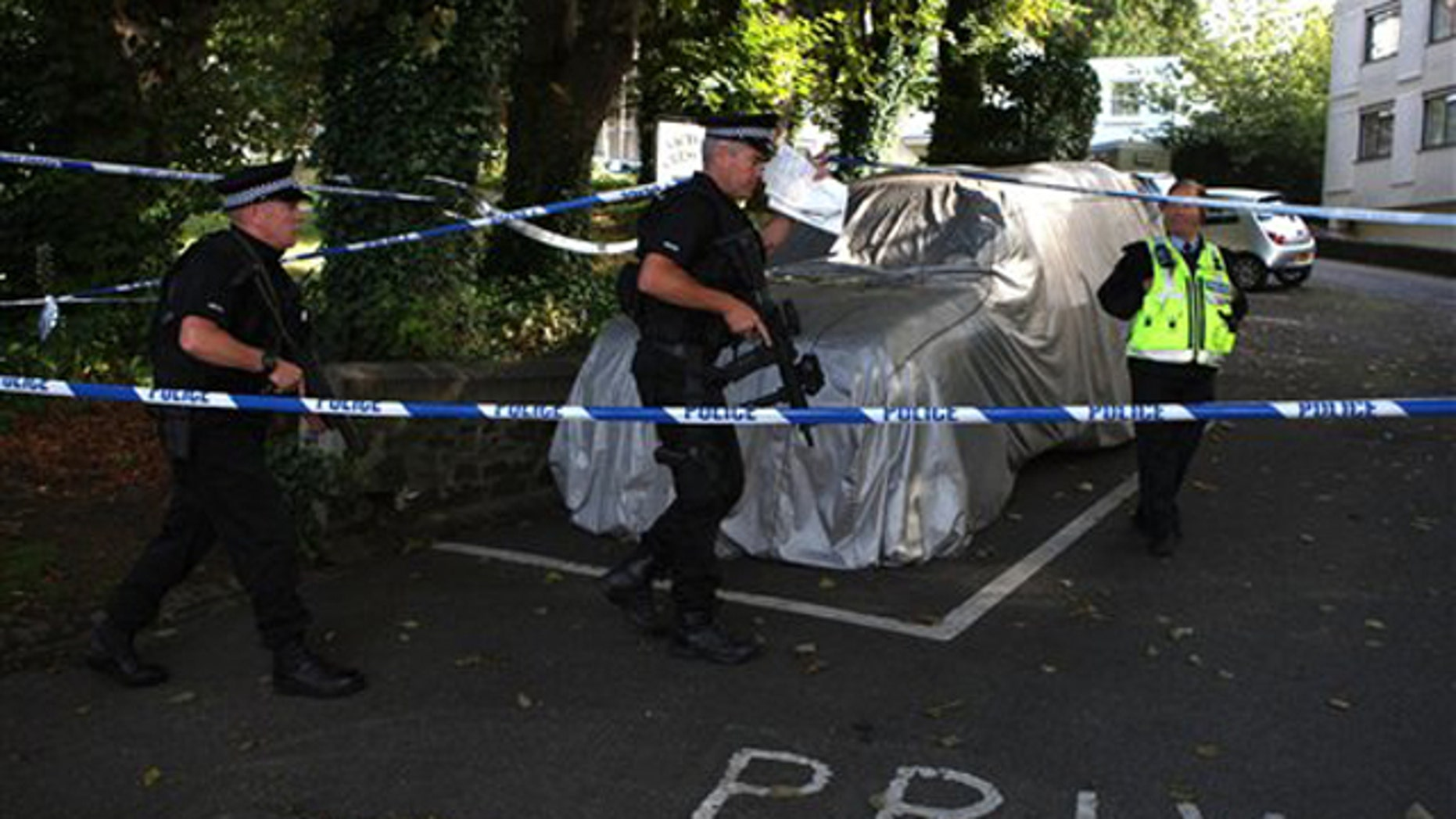 Armed police walk through the grounds of Victoria Crescent in St Helier, Jersey, Monday Aug. 15, 2011. A man was arrested on suspicion of stabbing six people to death, including three children, on the British island of Jersey in what was the deadliest crime in the community's living memory, police said. (AP Photo/Steve Parsons, PA) UNITED KINGDOM OUT NO SALES NO ARCHIVE