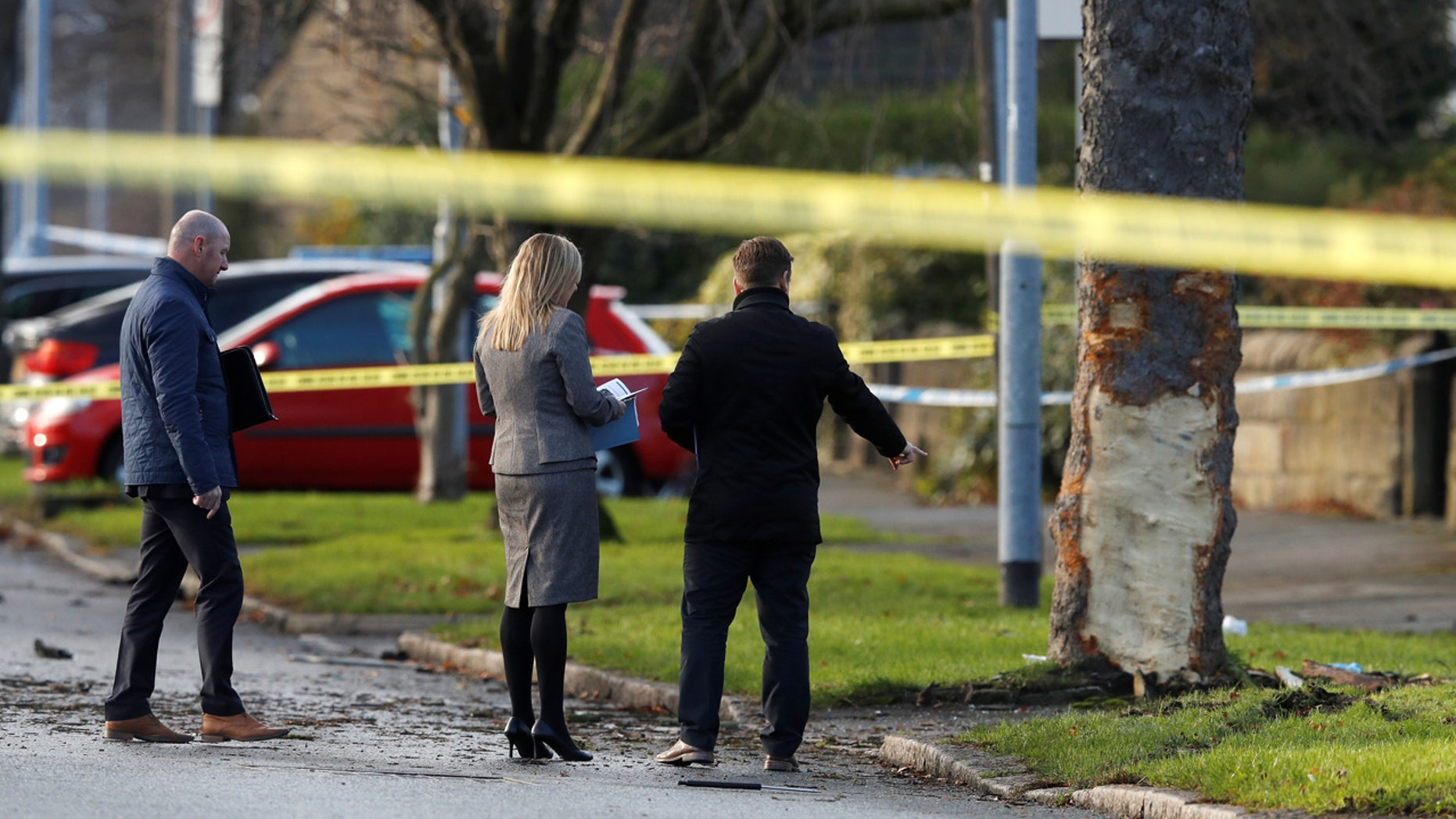 Investigators work behind police tape at the scene where a stolen car crashed into a tree, leaving 5 people dead, including 3 children, in Leeds, Britain,