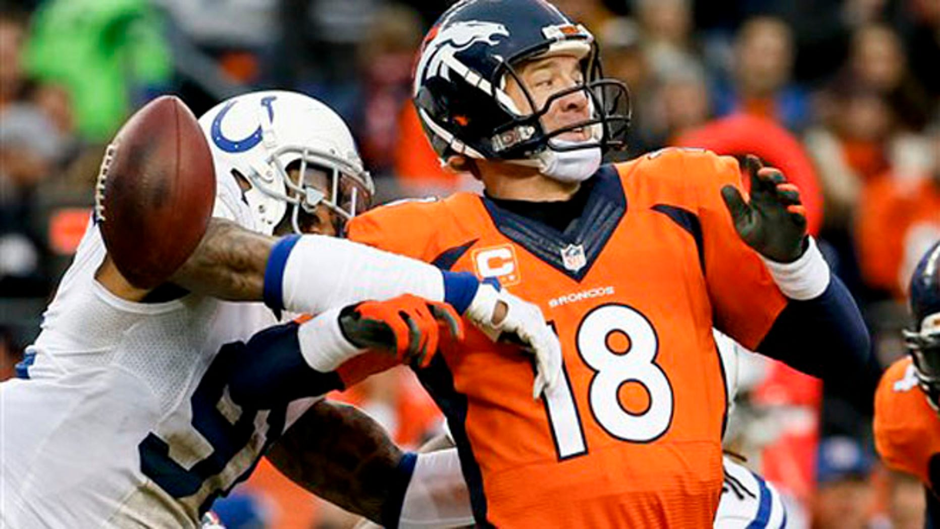 Jan. 11, 2015: Indianapolis Colts linebacker Jonathan Newsome, left, reaches in to force Denver Broncos quarterback Peyton Manning fumble during the first half of an NFL divisional playoff football game.