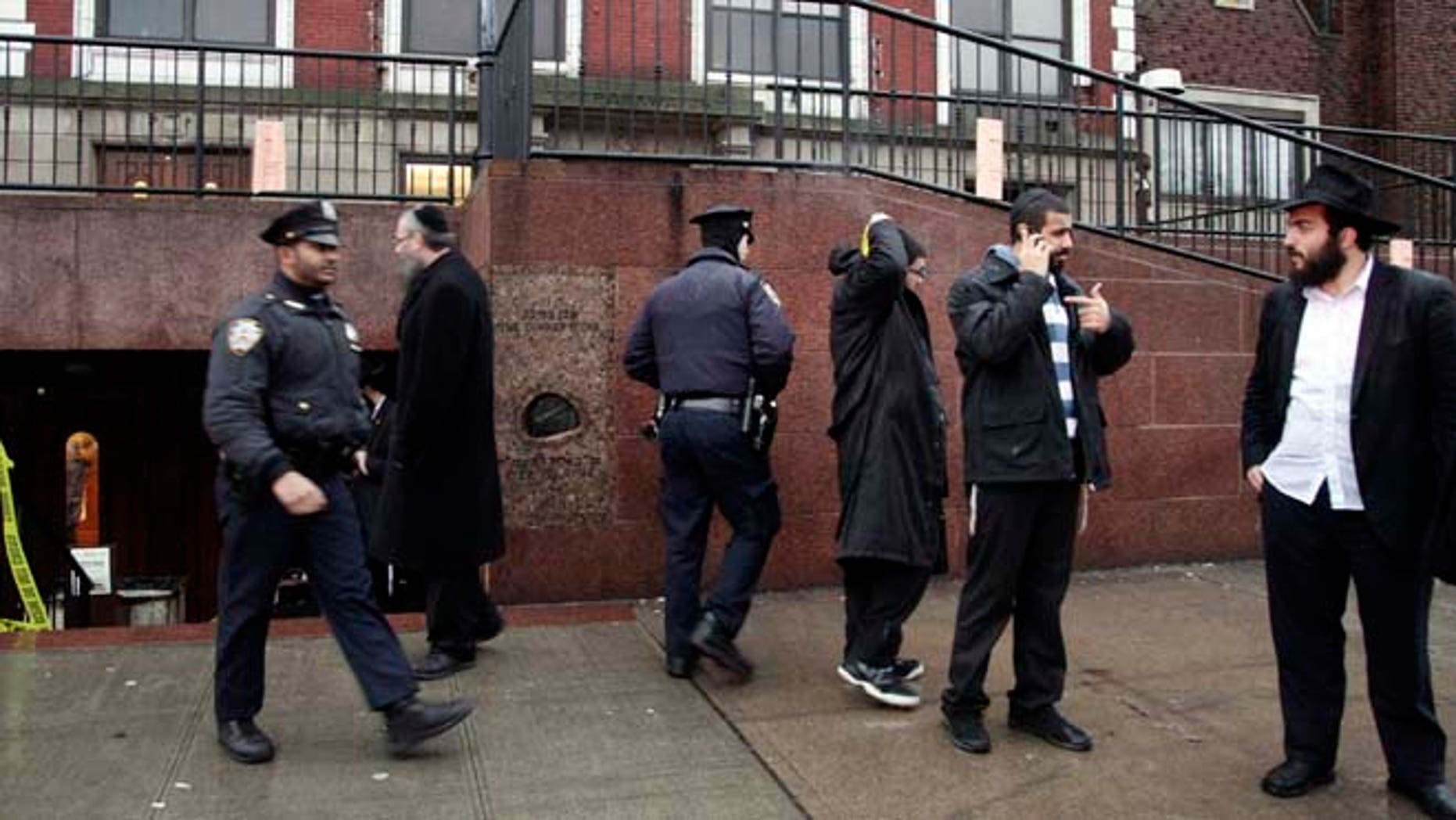 Dec. 9, 2014: Members of the Lubavitch community and police officers stand outside Chabad-Lubavitch Hasidic headquarters, in New York.