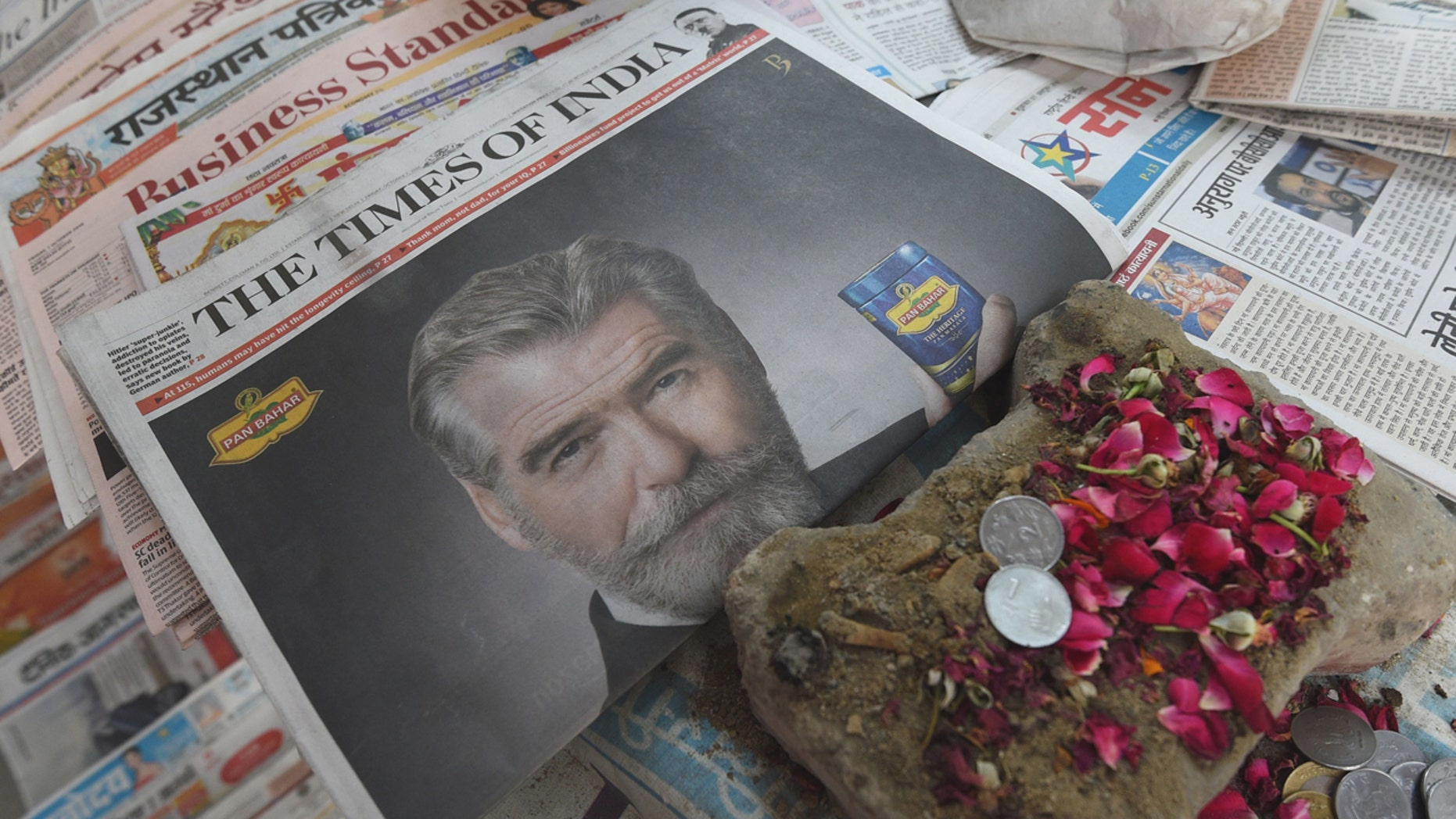 A newspaper with a front page advertisment of former 007 star Pierce Brosnan endorsing an Indian mouth freshener, is seen on the streets of New Delhi on October 7, 2016. Former 007 star Pierce Brosnan sparked ridicule on social media October 7, 2016 by starring in a new James Bond-style spoof commercial for an Indian mouth freshener that left fans shaken and stirred. / AFP / DOMINIQUE FAGET        (Photo credit should read DOMINIQUE FAGET/AFP/Getty Images)
