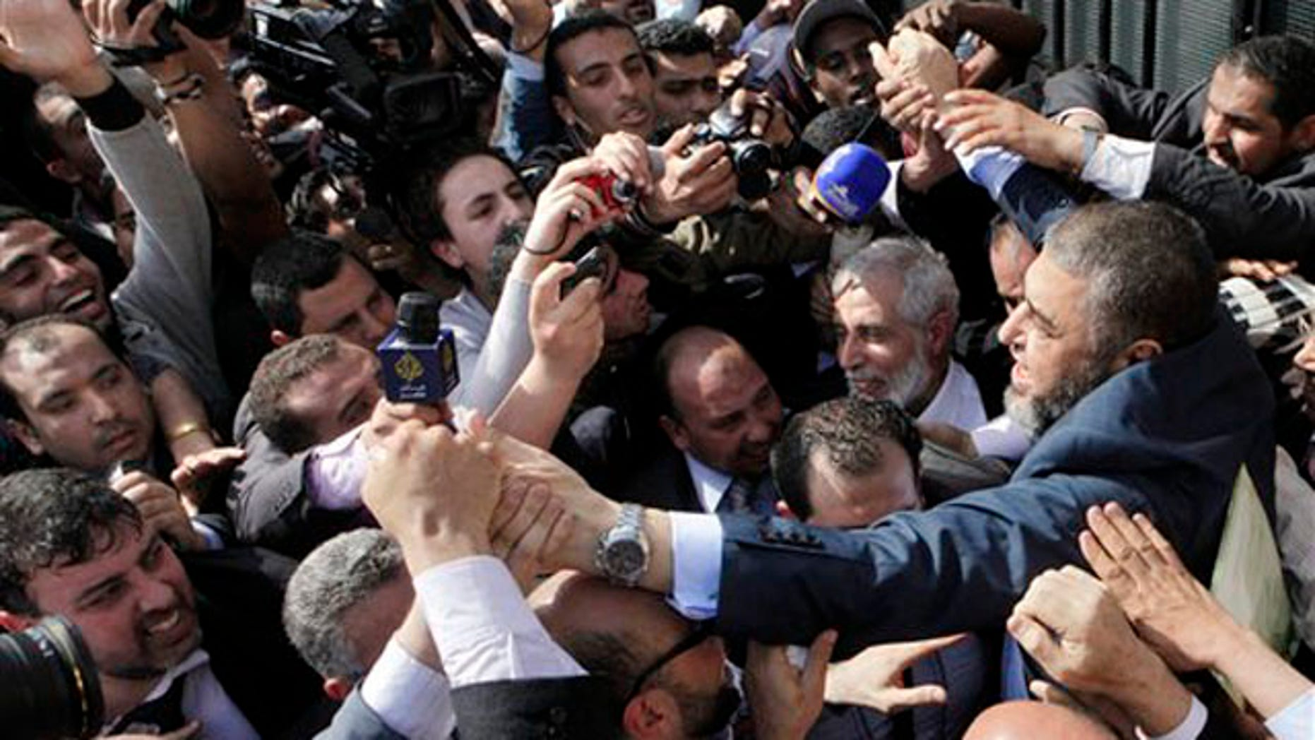 April 5, 2012: Muslim Brotherhood presidential hopeful Khairat el-Shater, right, is surrounded by hundreds of supporters and cameramen in Cairo.