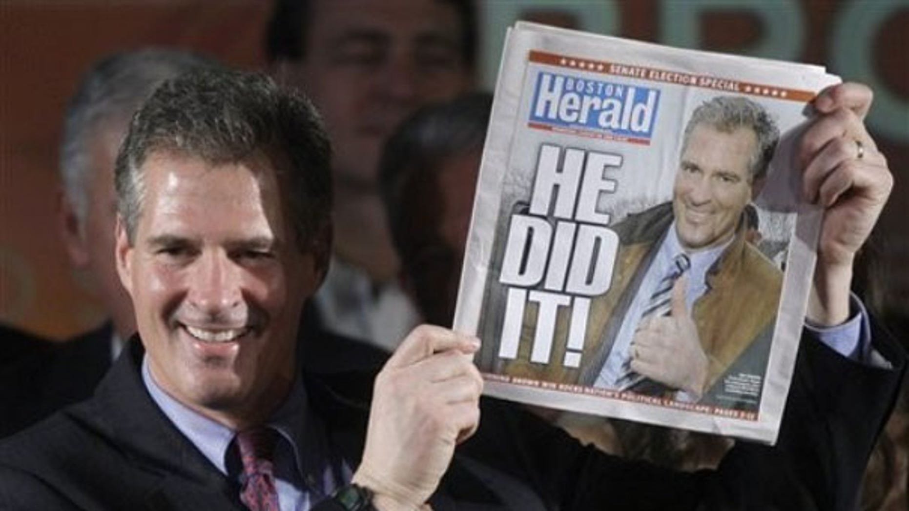 Scott Brown holds up a copy of the Boston Herald as he celebrates his election victory in Boston Jan. 19. (AP Photo)