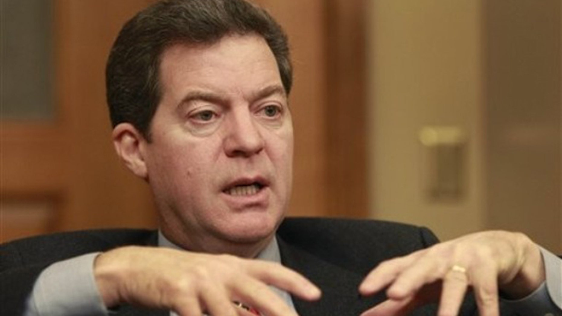 In this Dec. 21, 2010 photo, Kansas Gov. Sam Brownback is shown before taking office talking with a reporter in Topeka.