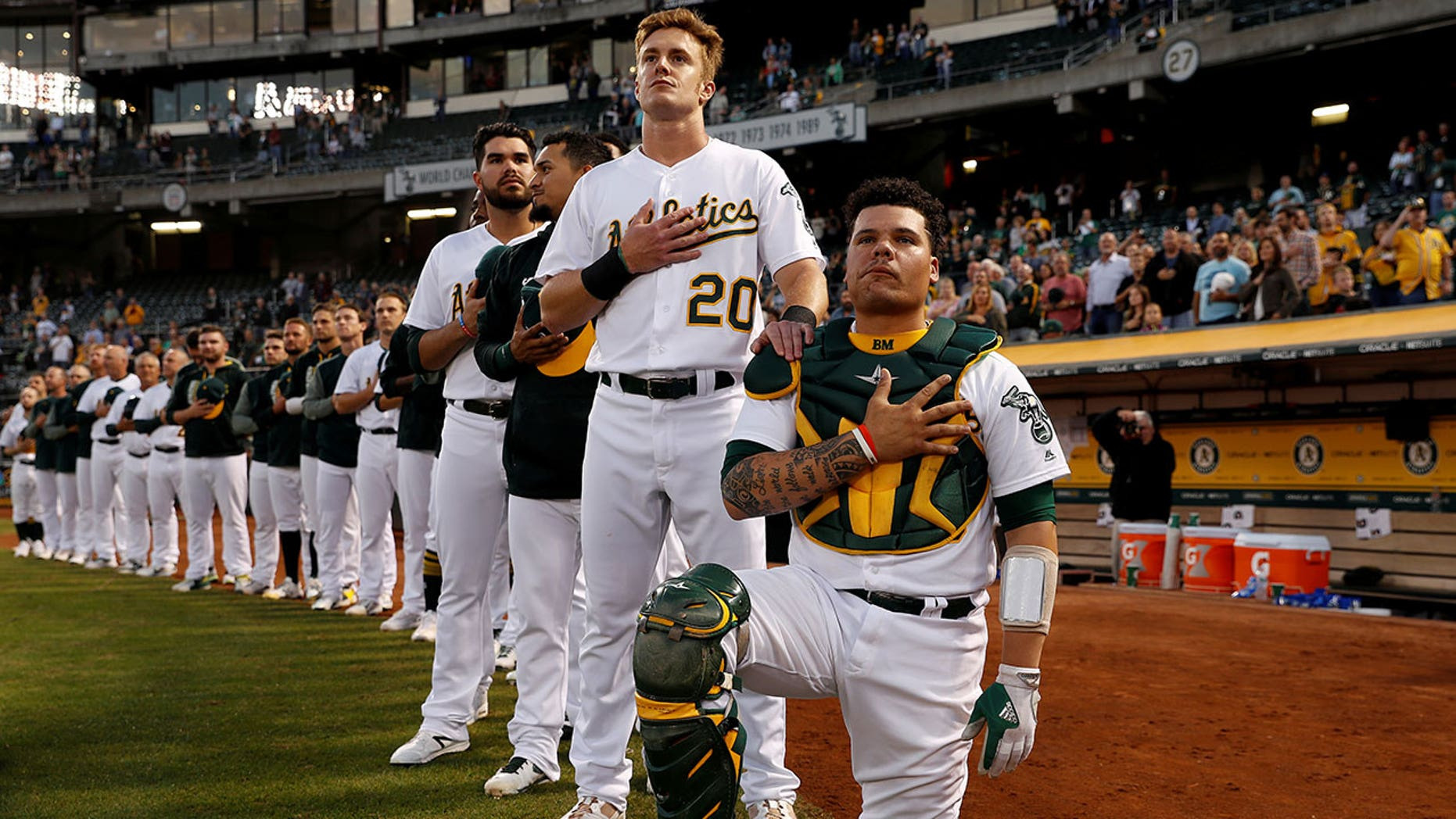 Bruce Maxwell of the Oakland Athletics kneels as teammate Mark Canha #20 places his hand on Maxwell's shoulder during the singing of the national anthem on September 25.