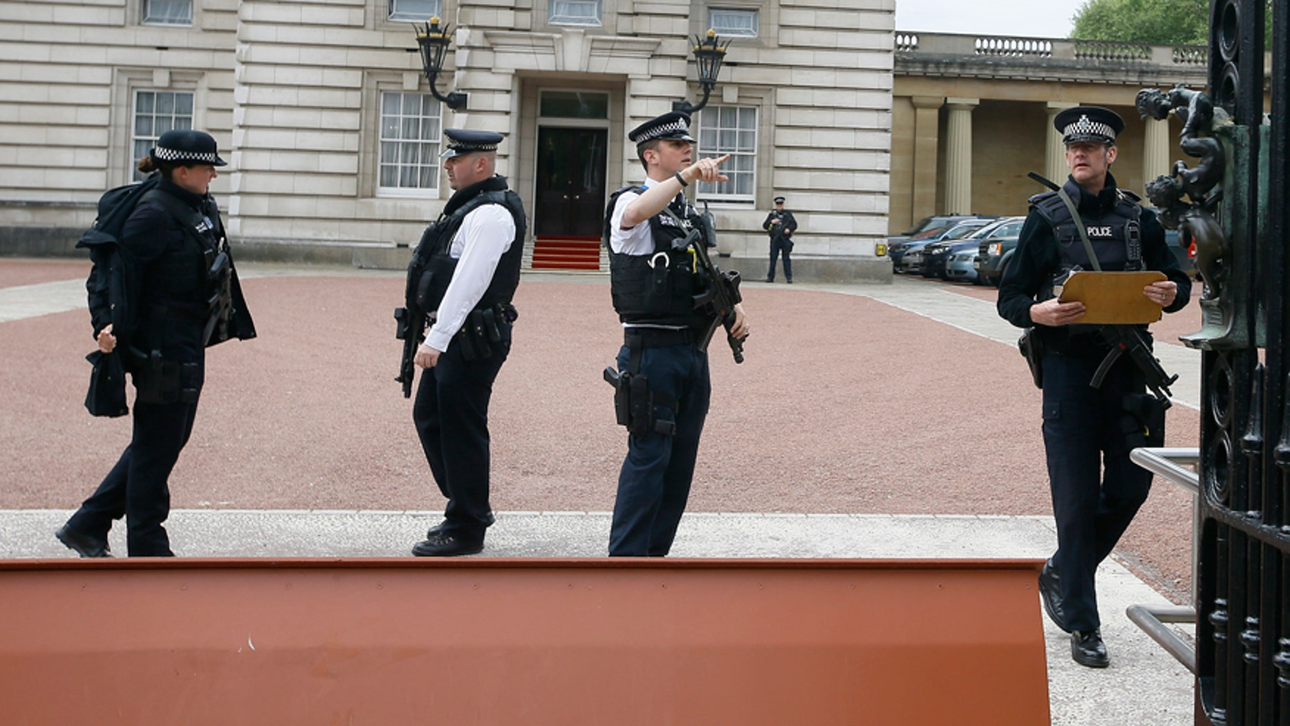 May 19, 2016: Armed police officers work at the main gate of Buckingham Palace in London.