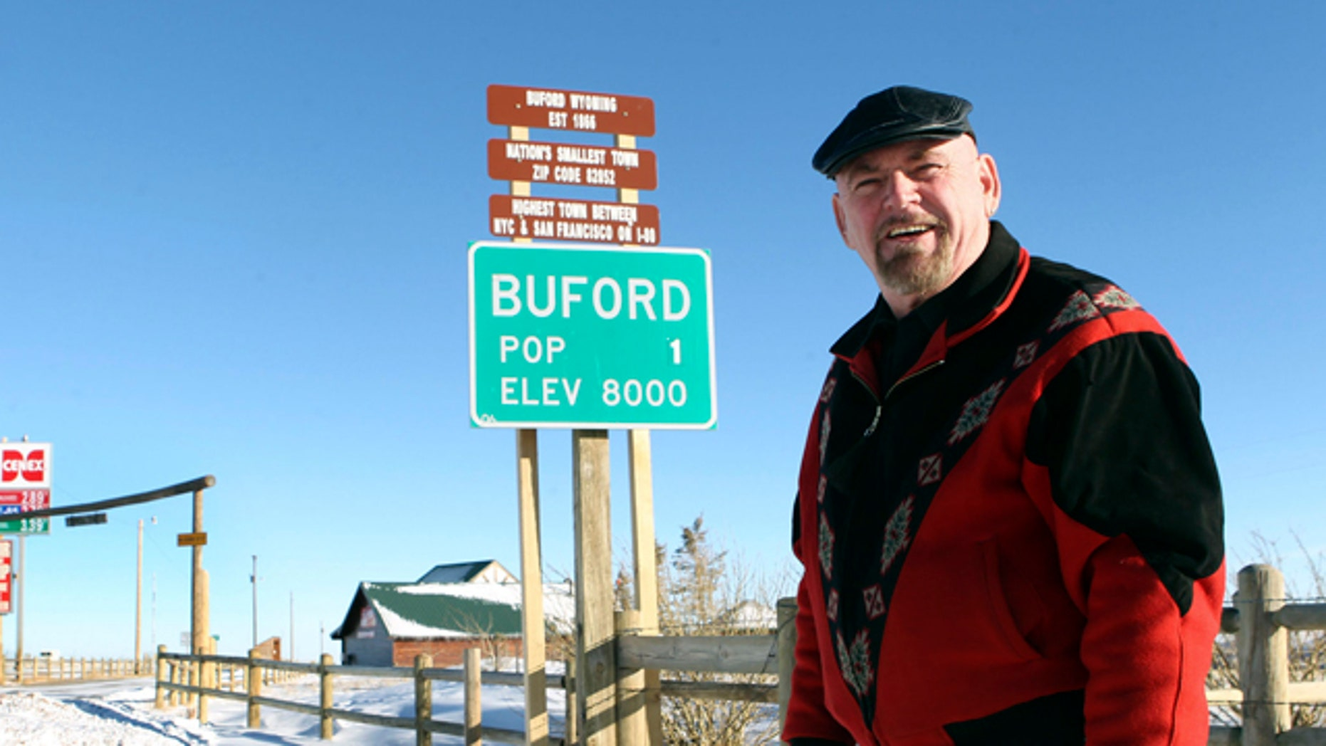 This Jan. 1, 2011 file photo shows Buford resident Don Sammons standing in front of the population sign in Buford, Wyo. The town advertised as the smallest in the United States has sold at auction for $900,000.