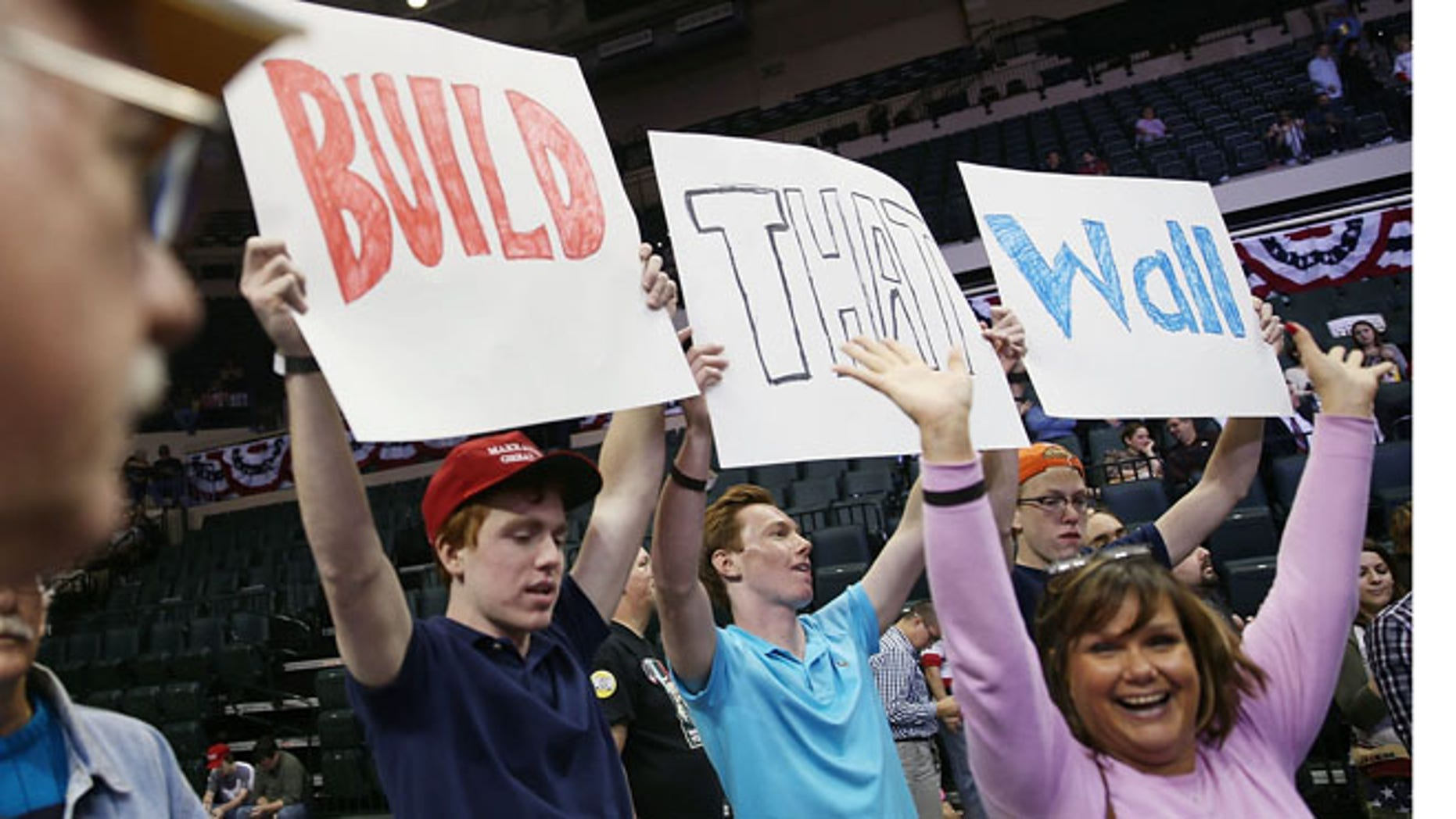 "People hold signs that read, "" Build that Wall"", as they wait for Republican presidential candidate Donald Trump on Feb. 12, 2016 in Tampa, Fla. (Joe Raedle/Getty Images)"