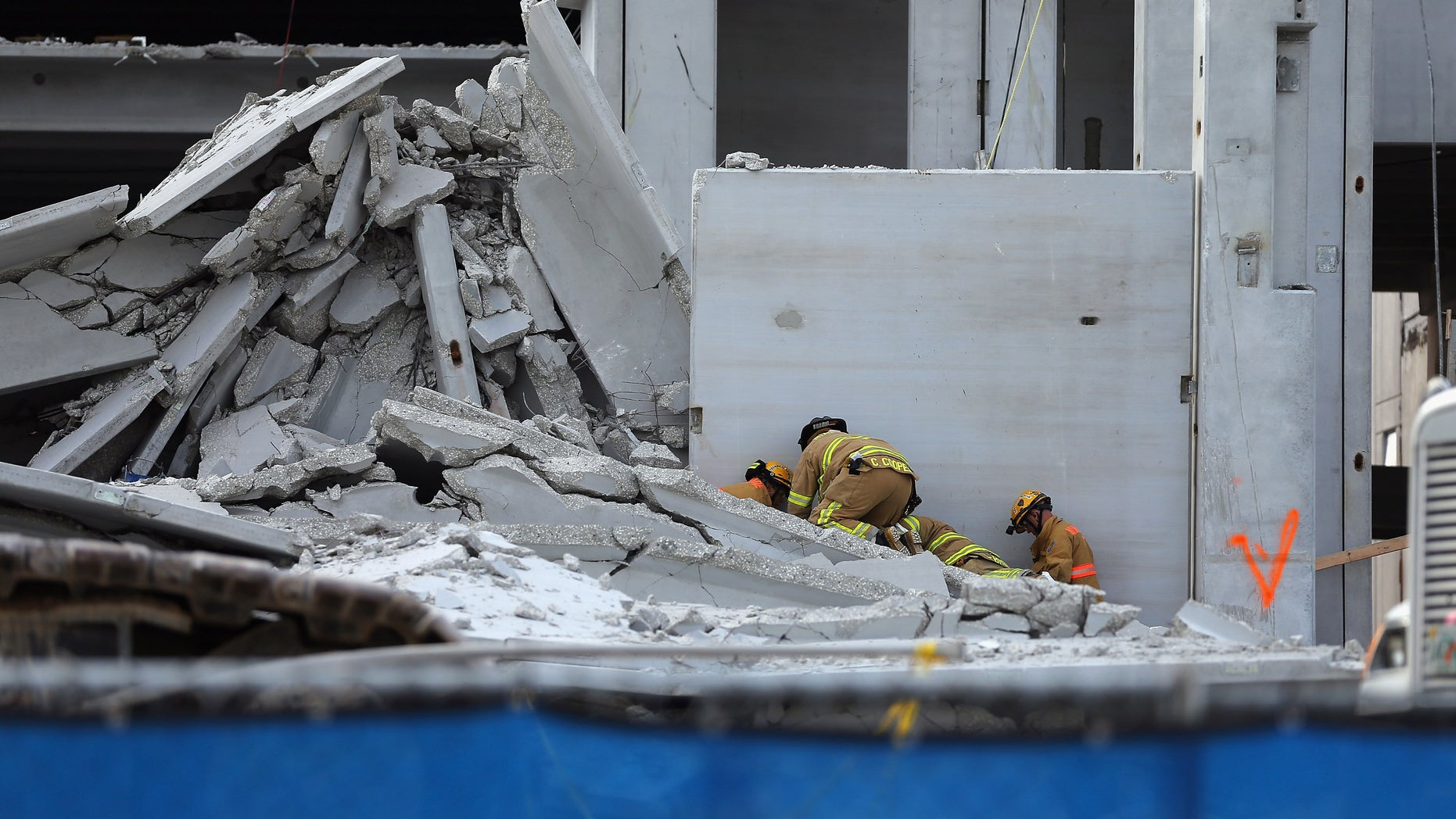 DORAL, FL - OCTOBER 10:  Miami-Dade Rescue workers prepare to pull a body out of the rubble of a four-story parking garage that was under construction and collapsed at the Miami Dade College?s West Campus on October 10, 2012 in Doral, Florida.  Early reports indicate that one person was killed in the collapse, at least seven people injured and one person may still be trapped in the rubble.  (Photo by Joe Raedle/Getty Images)