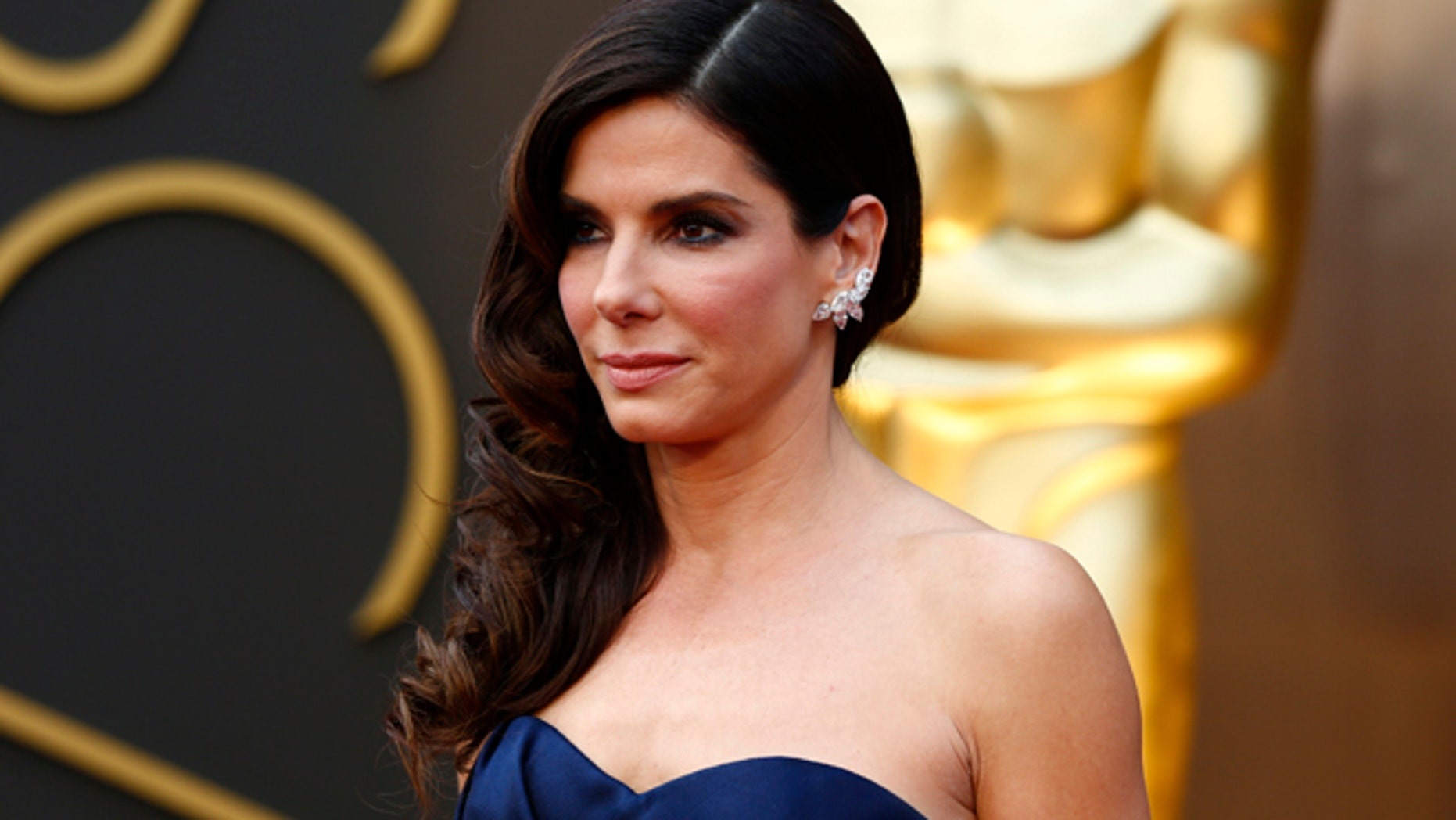 """Mar 2, 2014: Sandra Bullock, best actress nominee for her role in """"Gravity,""""  wearing a navy Alexander McQueen gown  with Lorraine Schwartz jewels, arrives at the 86th Academy Awards in Hollywood, California."""