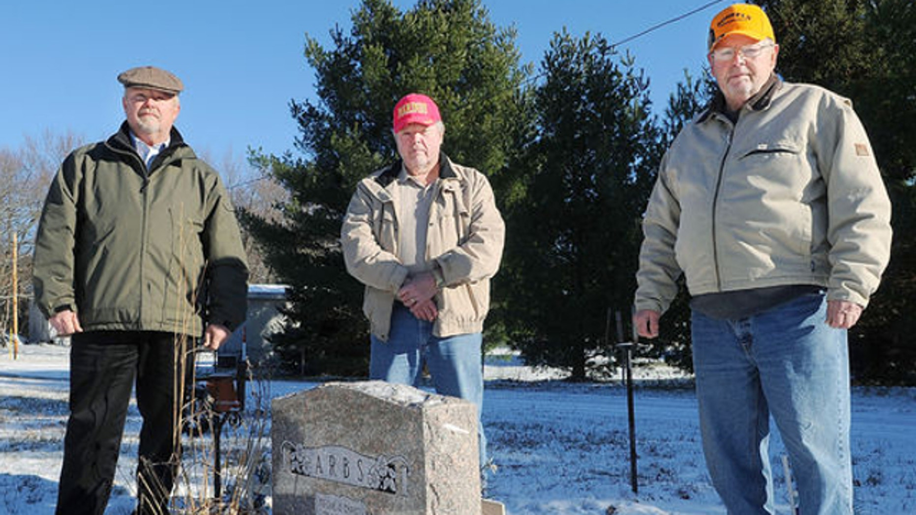 """Nov. 22, 2013: Brothers, from left, Dean, David and Louis """"Andy"""" Arbs, pose at the family grave site of their grandparents, Louis and Anny Arbs, at Oak Grove Cemetery in Eau Claire, Wis."""