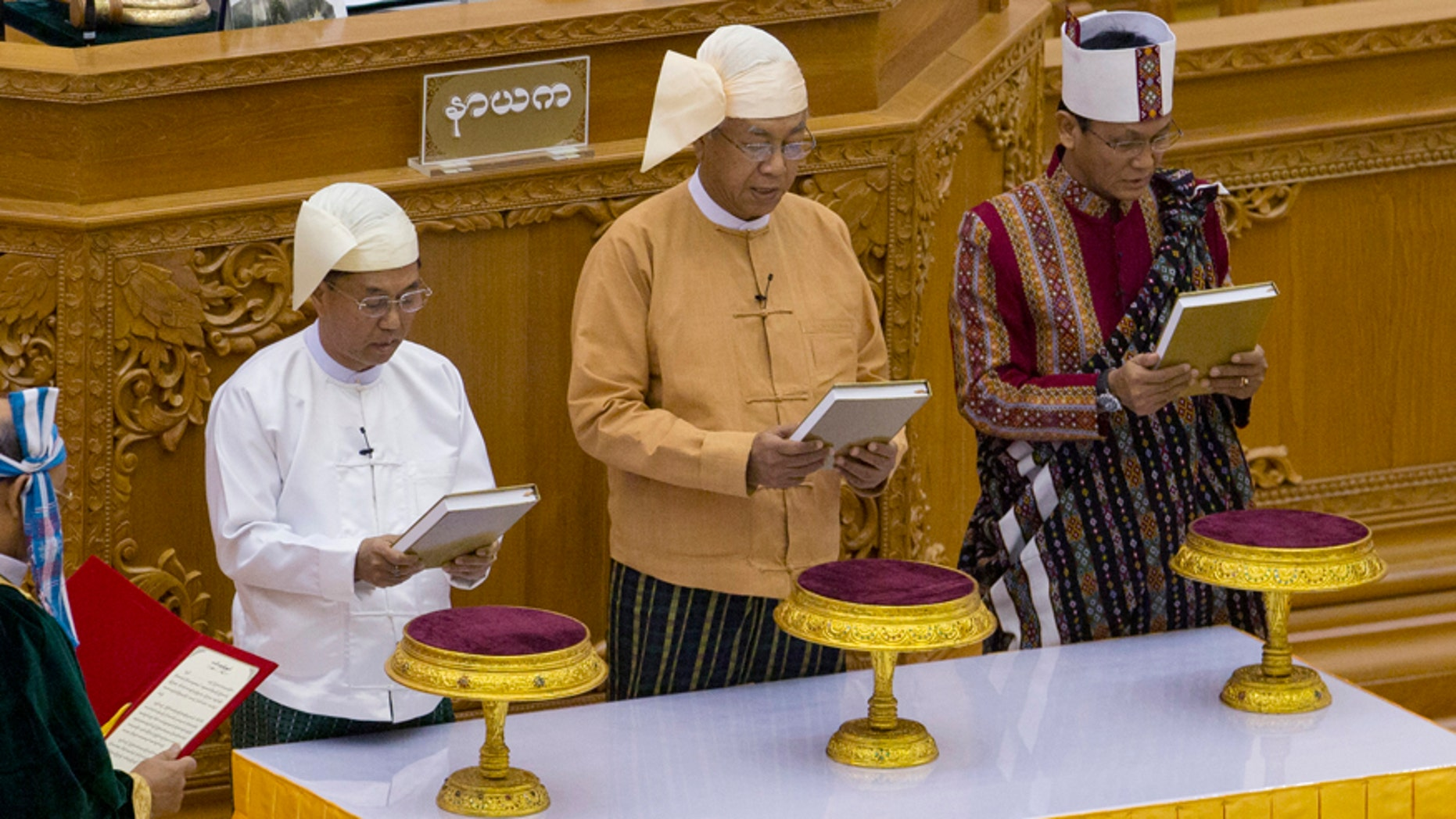 March 30, 2016: Lawmakers from right, Henry Van Hti Yu as seconnd vice president, Htin Kyaw as president and Myint Swe as first-vice president, take oaths during a ceremony in parliament in Naypyitaw, Burma.